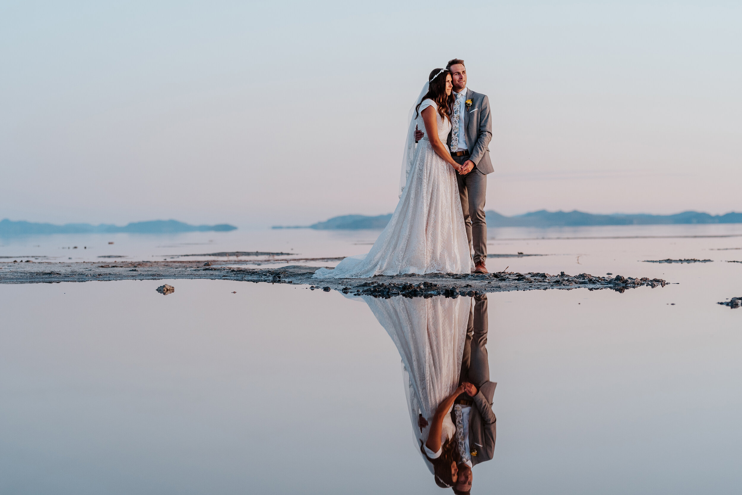 Stunning last moments of sunlight as the bride and groom stand together with their reflections in the water watching the sun disappear beyond the distant mountain ranges in Northern Utah. #spiraljetty #GreatSaltLake #formalsession #SaltFlats #sunsetphotosession #NorthernUtah #weddingphotographer #formalphotographer #brideandgroom #outdoorformals #weddingformalphotography