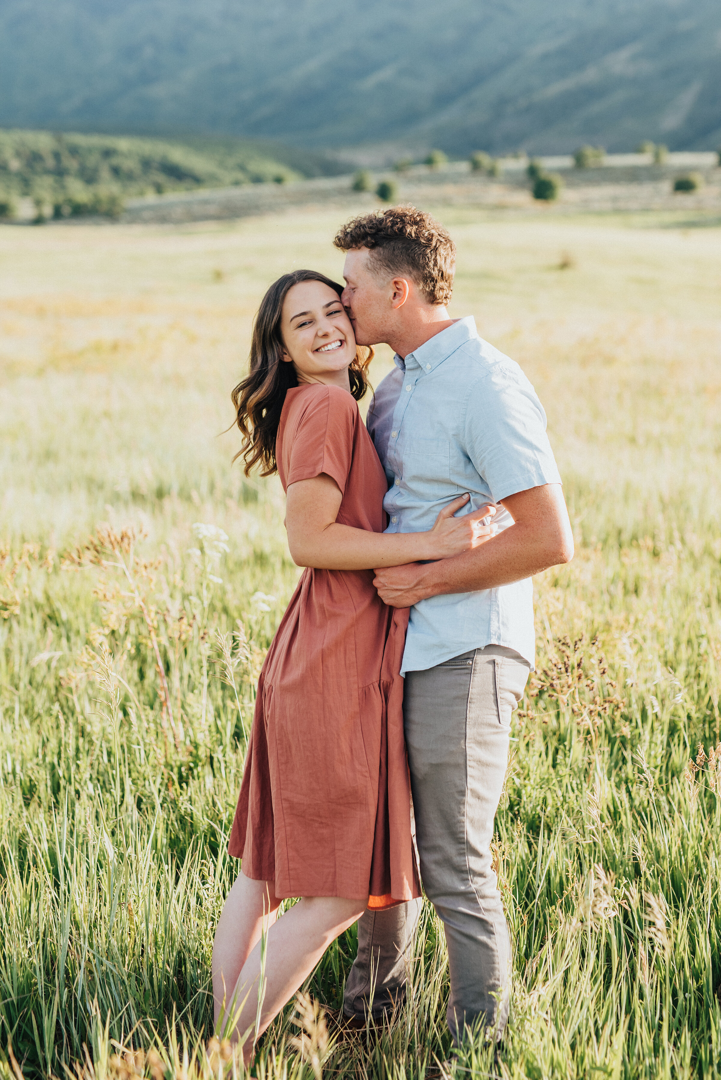 Sunset engagement session with adorable utah couple by professional engagement photographer Kristi Alyse Photography shooting in Cache Valley, Utah near the Wellsville Mountains. mountain engagement session yellow fields sunset engagement pictures outfit inspiration for engagement photos with Kristi Alyse in logan utah #engagements #loganutahphotographer #posingideas #engagementphotos #utahbride #professionalengagements #engagementinspo #couplesphotography #wellsville #mountainengagements