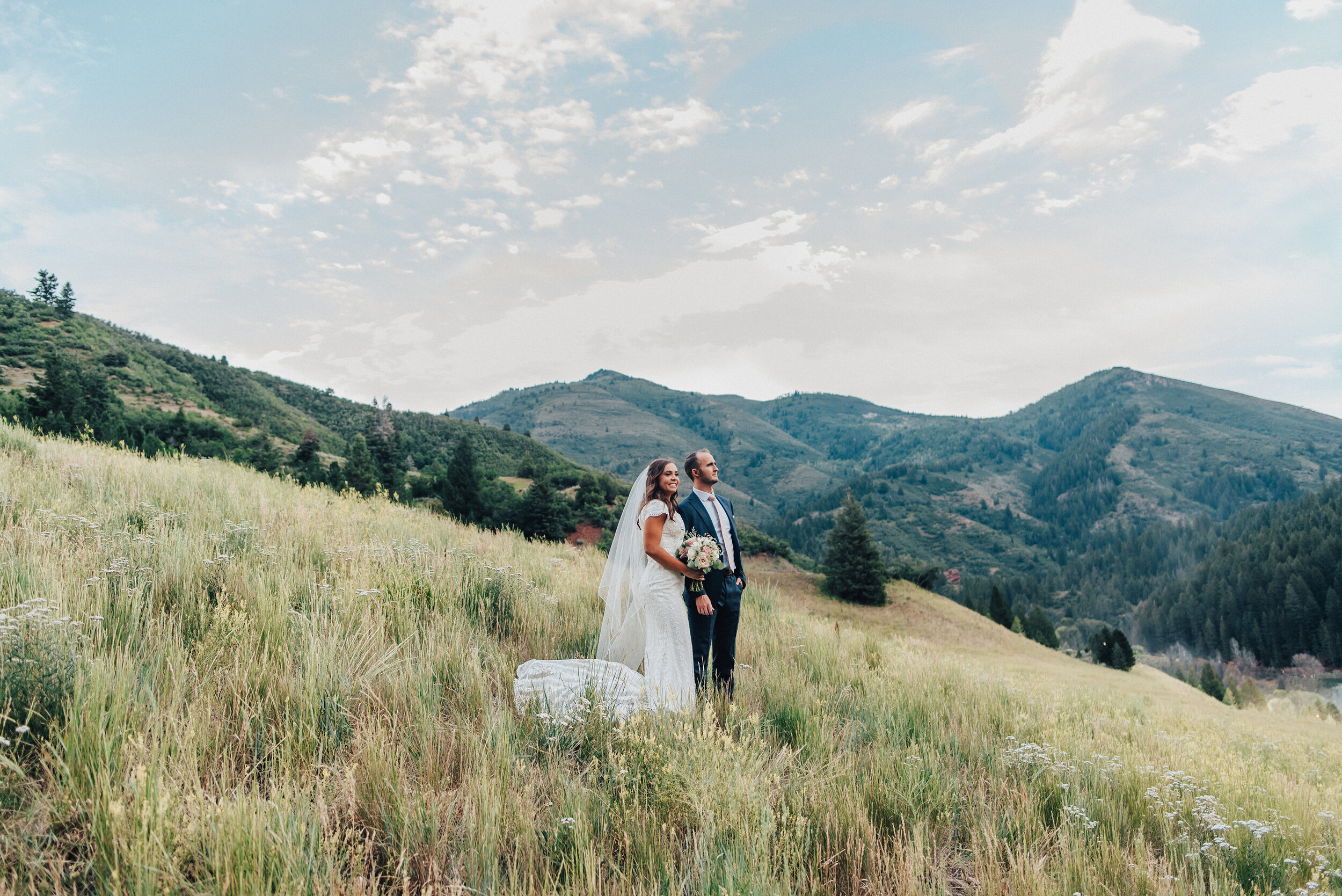A beautiful couple overlook the Tibble Fork Reservoir while standing on a gorgeous grassy hillside in American Fork Canyon. Mountains in the background evergreen trees couple posed looking forward utah photography wide landscape tall grass navy suit light pink bouquet #husbandandwife #younglove #tibbleforkreservoir #utahwedding #americanforkcanyon #coupleshoot #formals #weddingphotography #couplesgoals #couplephotography #weddingphotographer #couplesphotography #groom #bride