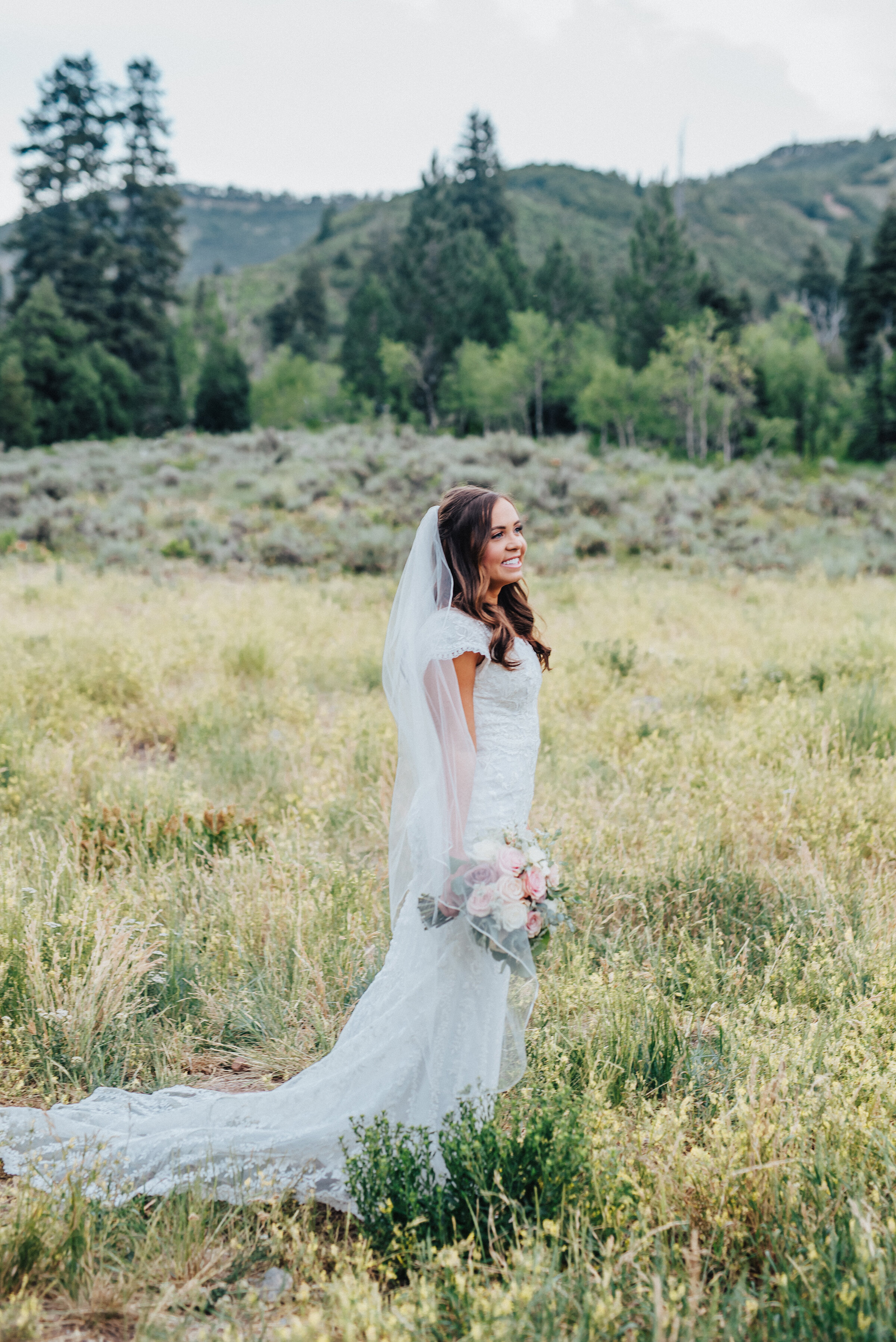 A lovely bride holds her bouquet tightly at her side while smiling and looking across a grassy field in American Fork canyon. Tibble Fork reservoir overlook grassy hillside evergreen trees woodsy scenery bridal shot light pink bouquet mountains in the background long veil #bridals #younglove #tibbleforkreservoir #utahwedding #americanforkcanyon #coupleshoot #formals #weddingphotography #couplesgoals #couplephotography #weddingphotographer #pinkbouquet #bride #rollinghills
