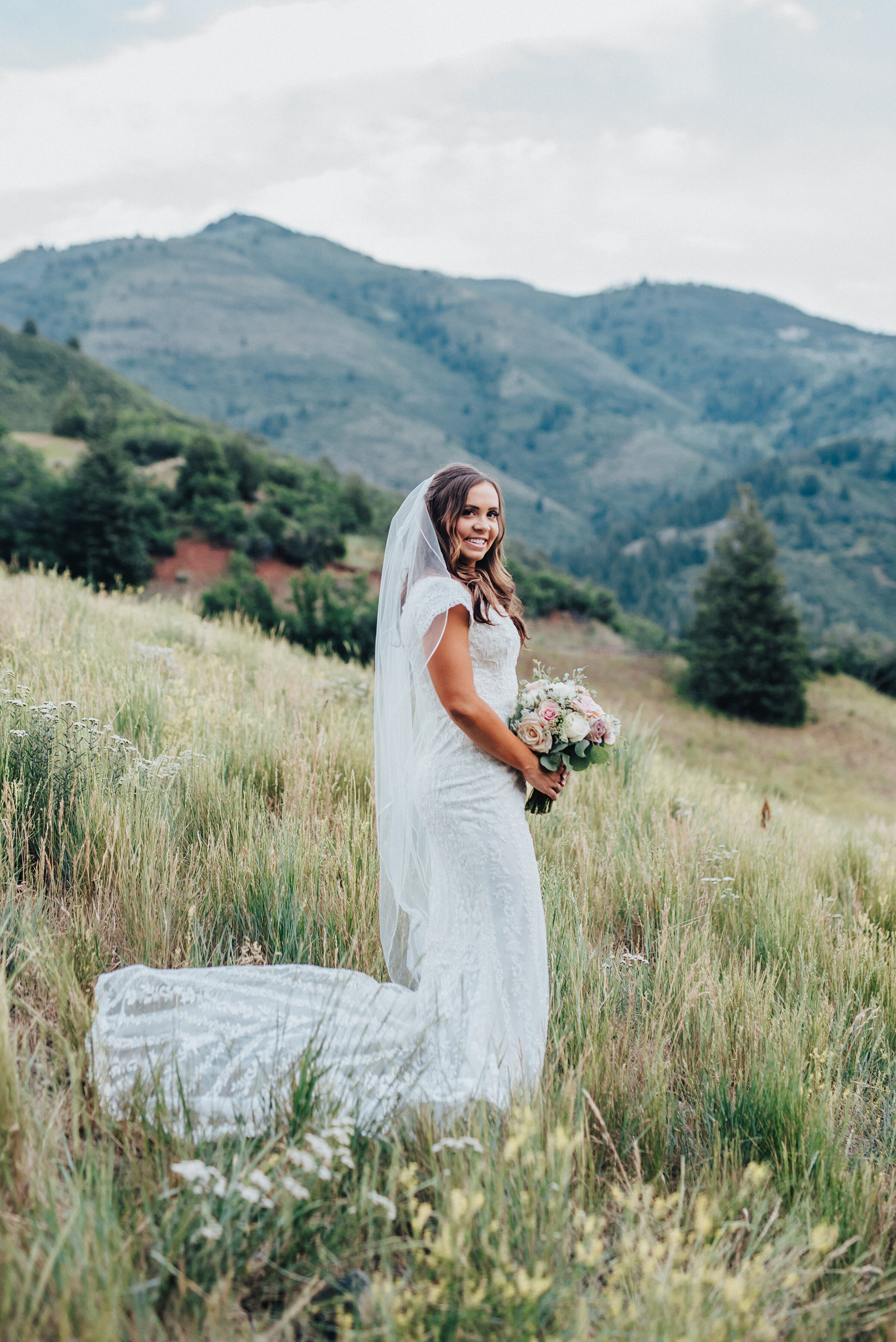 A gorgeous bride holds her bouquet in a traditional position while smiling and looking into the camera on a grassy hillside in American Fork canyon. Tibble Fork reservoir overlook grassy hillside evergreen trees woodsy scenery bridal shot light pink bouquet mountains in the background long veil #bridals #younglove #tibbleforkreservoir #utahwedding #americanforkcanyon #coupleshoot #formals #weddingphotography #couplesgoals #couplephotography #weddingphotographer #pinkbouquet #bride #rollinghills