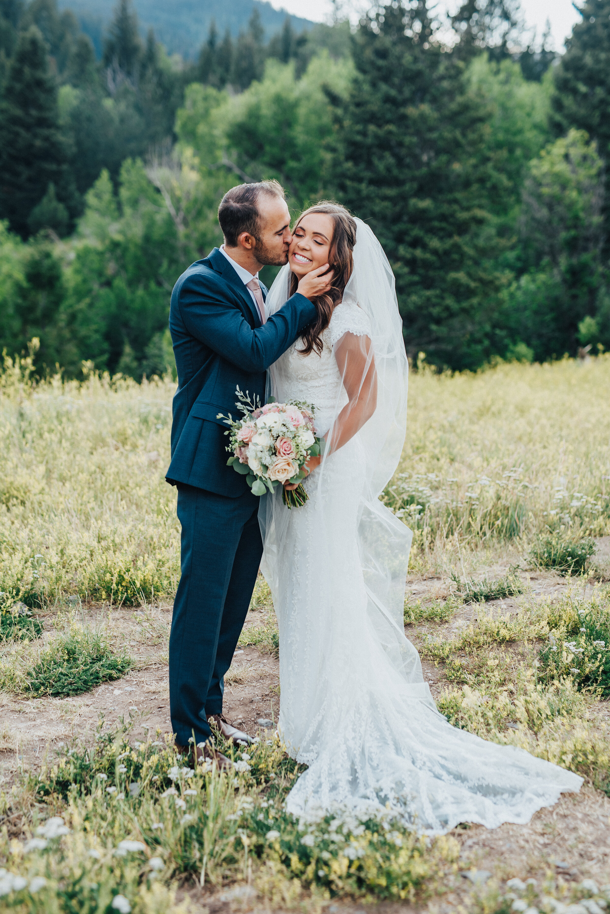 A smitten husband gently caresses his smiling bride's cheek while giving her a soft kiss.holding bouquet in traditional position evergreen trees eyes closed utah photography landscape navy blue suit light pink tie light pink bouquet #husbandandwife #younglove #tibbleforkreservoir #utahwedding #americanforkcanyon #coupleshoot #formals #weddingphotography #couplesgoals #couplephotography #weddingphotographer #couplesphotography #groom #bride