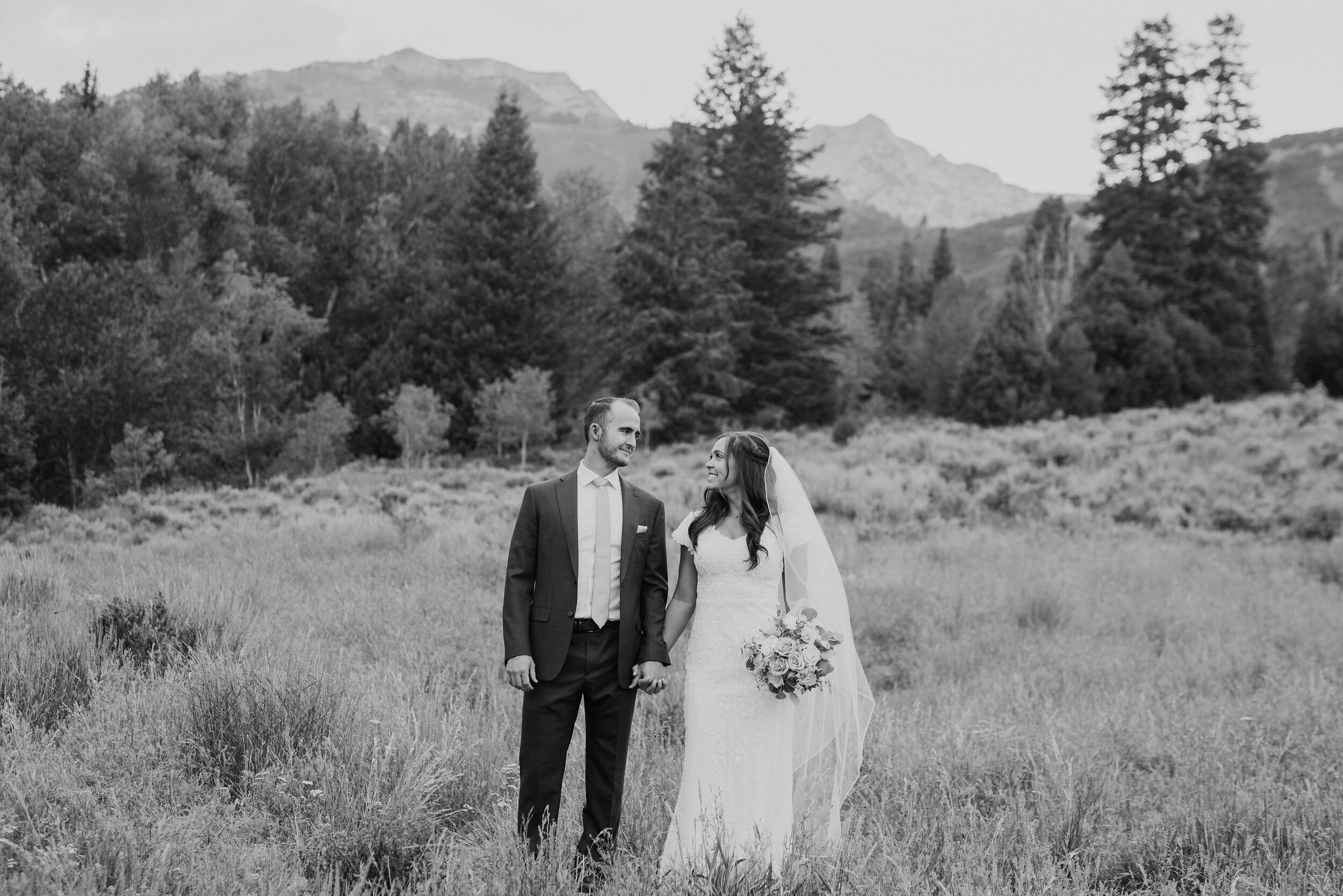 A classic black and white shot of a lovely couple looking into each other's eyes and smiling while strolling in tall grass. Holding hands walking through the grass evergreen trees black and white photography exchanged looks wide landscape #husbandandwife #younglove #tibbleforkreservoir #utahwedding #americanforkcanyon #coupleshoot #formals #weddingphotography #couplesgoals #couplephotography #weddingphotographer #couplesphotography #groom #bride #blackandwhite