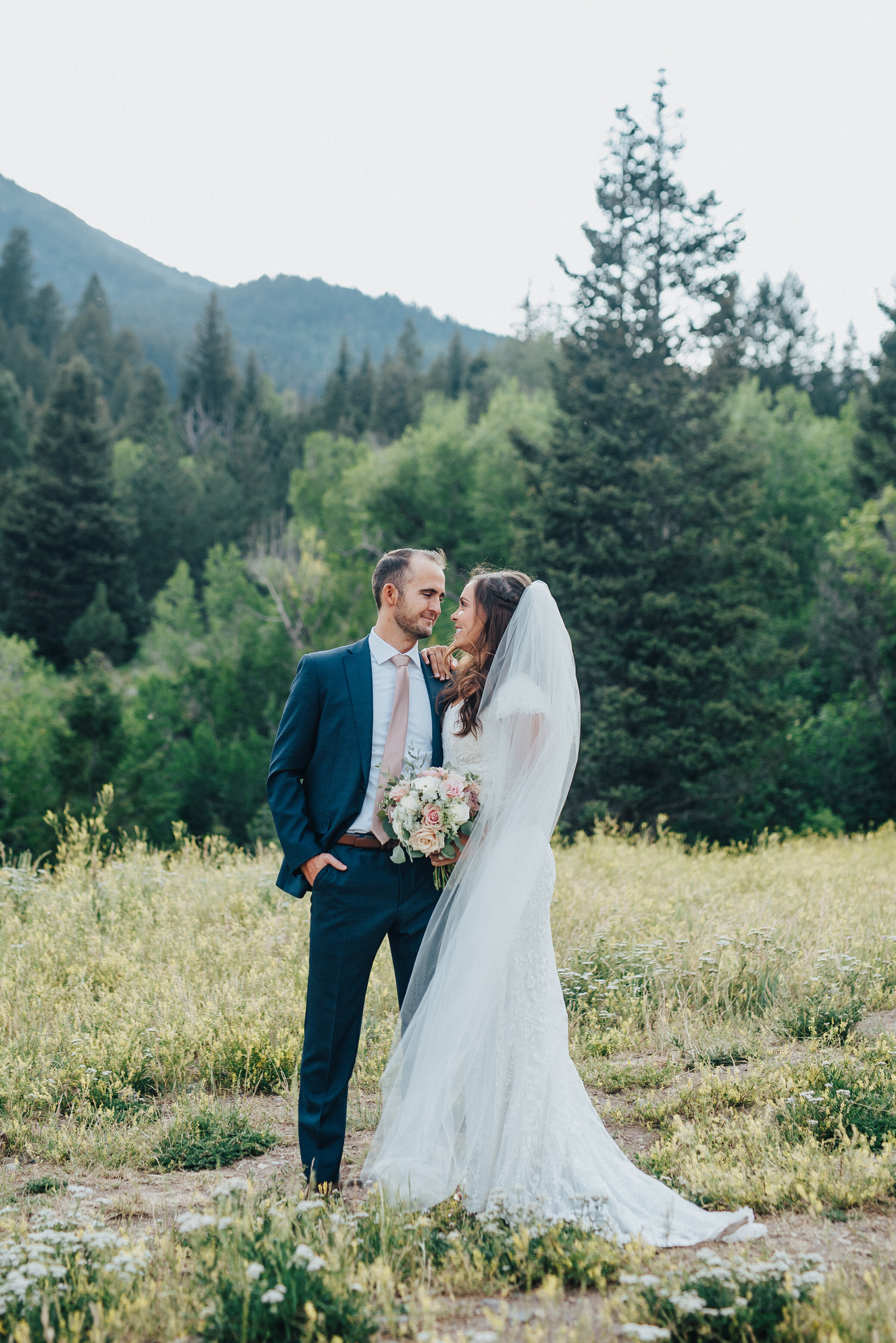An enamored couple looks at each other while standing in an open grassy area before the woods.Light pink bouquet and tie navy blue suit evergreen trees mountainside background grassy terrain American Fork Canyon Tibble Fork Reservoir full length veil #husbandandwife #younglove #tibbleforkreservoir #utahwedding #americanforkcanyon #coupleshoot #formals #weddingphotography #couplesgoals #couplephotography #weddingphotographer #couplesphotography #groom #bride
