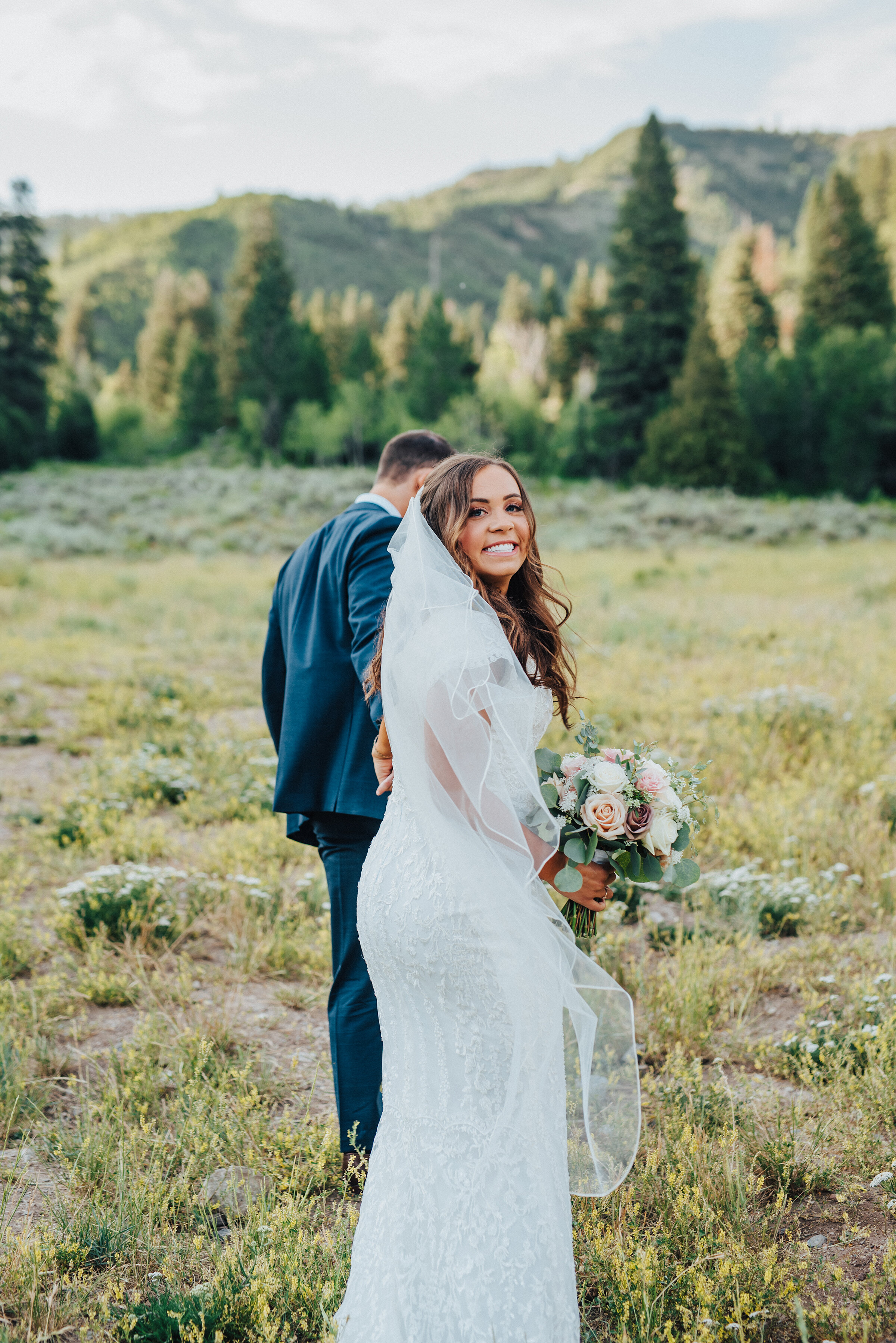 A smiling bride looks behind her as her husband gently tugs her forward towards the beautiful mountainside in American Fork Canyon. Light pink bouquet navy suit strolling in the grass evergreen trees husband and wife holding hands mountains and evergreen trees #husbandandwife #younglove #tibbleforkreservoir #utahwedding #americanforkcanyon #coupleshoot #formals #weddingphotography #couplesgoals #couplephotography #weddingphotographer #couplesphotography #groom #bride