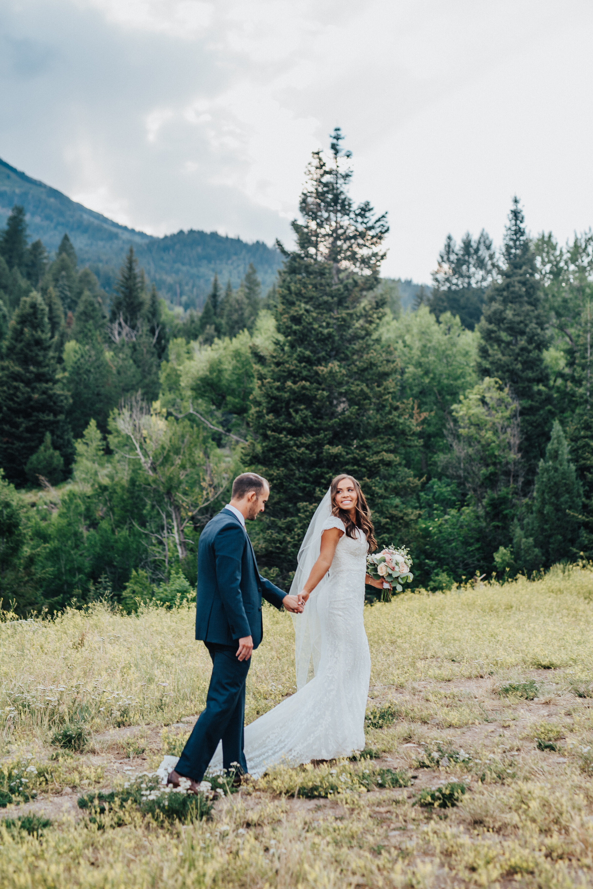 A smiling bride leads her husband by the hand as she strolls across an open grassy area in American Fork Canyon. Light pink bouquet and tie navy suit evergreen trees mountainside background grassy terrain American Fork Canyon Tibble Fork Reservoir holding hands full length veil #husbandandwife #younglove #tibbleforkreservoir #utahwedding #americanforkcanyon #coupleshoot #formals #weddingphotography #couplesgoals #couplephotography #weddingphotographer #couplesphotography #groom #bride