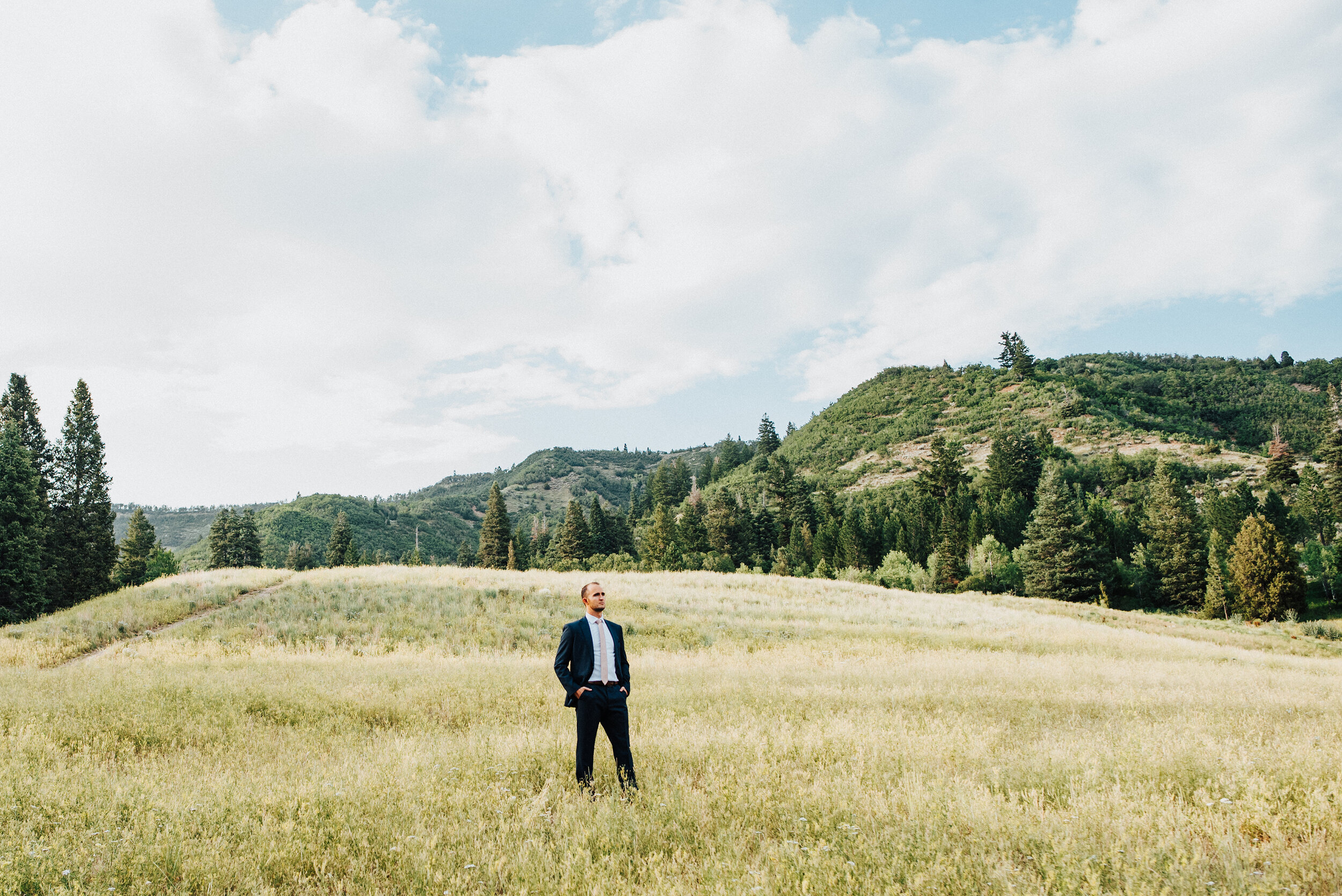 A handsome groom strikes a confident pose looking off into the distance with hands in his pockets in the middle of a grassy field. American Fork Canyon groom individual photo powerful pose navy suit light pink tie tall grass small mountains evergreen trees golden sunlight #newhusband #groomgoals #younglove #tibbleforkreservoir #utahwedding #americanforkcanyon #formals #weddingphotography #weddingphotographer #confidence #groomphoto #groom #individuals