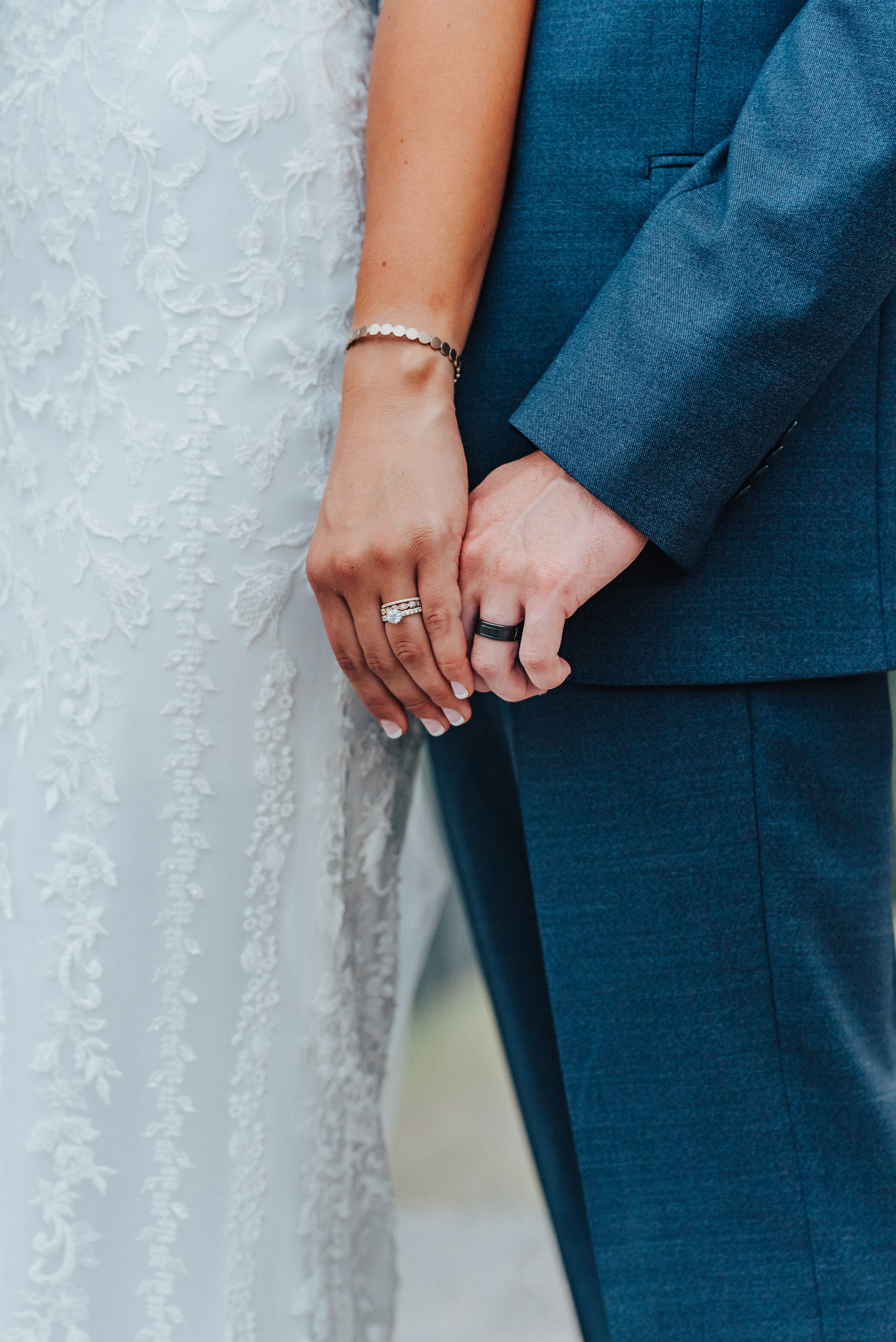 A close-up of the bride and groom's hands touching while showing off their gorgeous rings. Almost interlocked hands navy blue suit french tip nails close-up shot in American Fork floral dress design dark ring for the groom bride in front of groom #husbandandwife #younglove #tibbleforkreservoir #utahwedding #americanforkcanyon #coupleshoot #formals #weddingphotography #couplesgoals #couplephotography #weddingphotographer #couplesphotography #groom #bride #rings