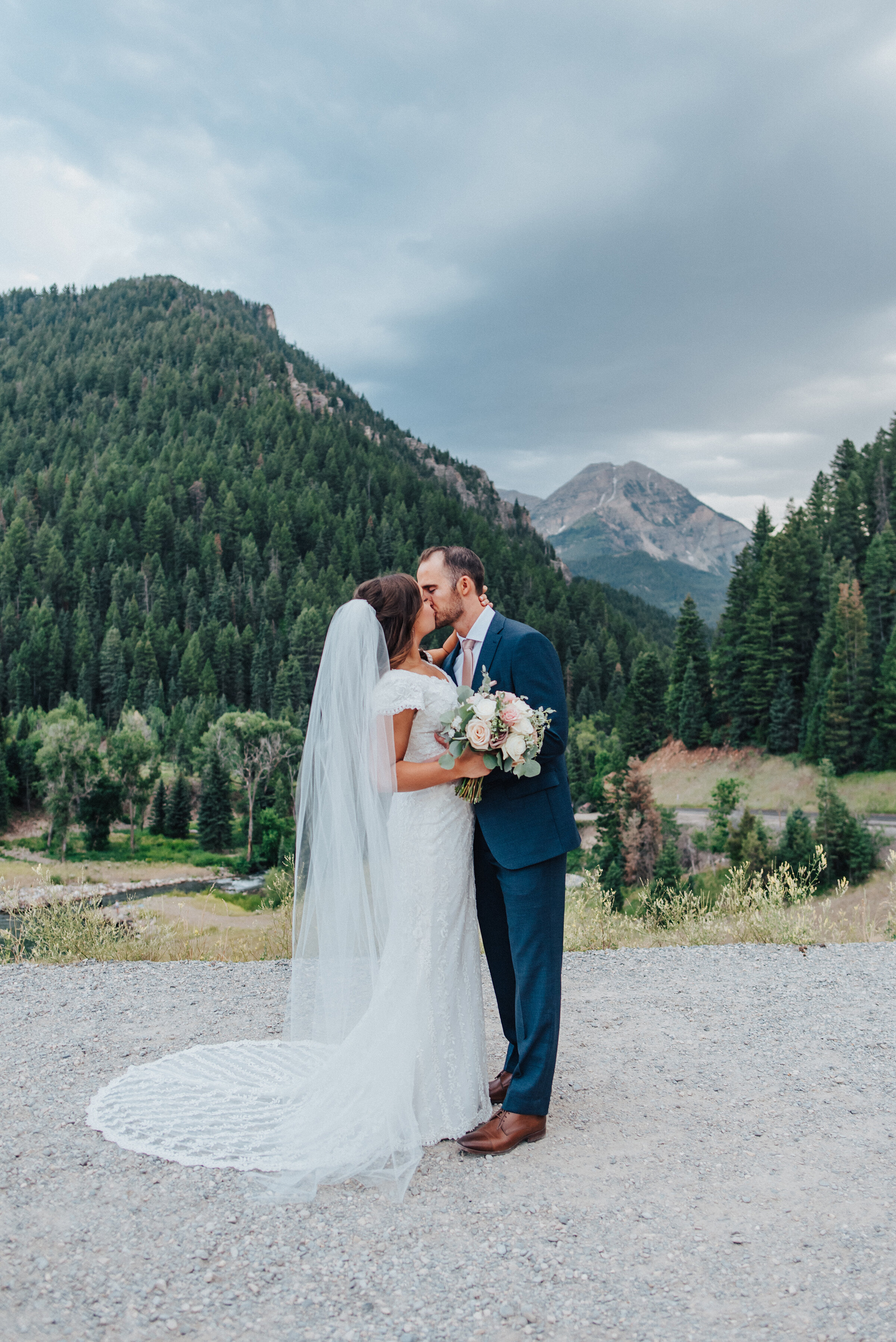 A beautiful couple shares a kiss while standing on a smooth sidewalk that surrounds the breathtaking Tibble Fork Reservoir. Navy suit light pink tie light pink floral bouquet exchanging glances evergreen trees mountains in the background #husbandandwife #younglove #tibbleforkreservoir #utahwedding #americanforkcanyon #coupleshoot #formals #weddingphotography #couplesgoals #couplephotography #weddingphotographer #couplesphotography #groom #bride