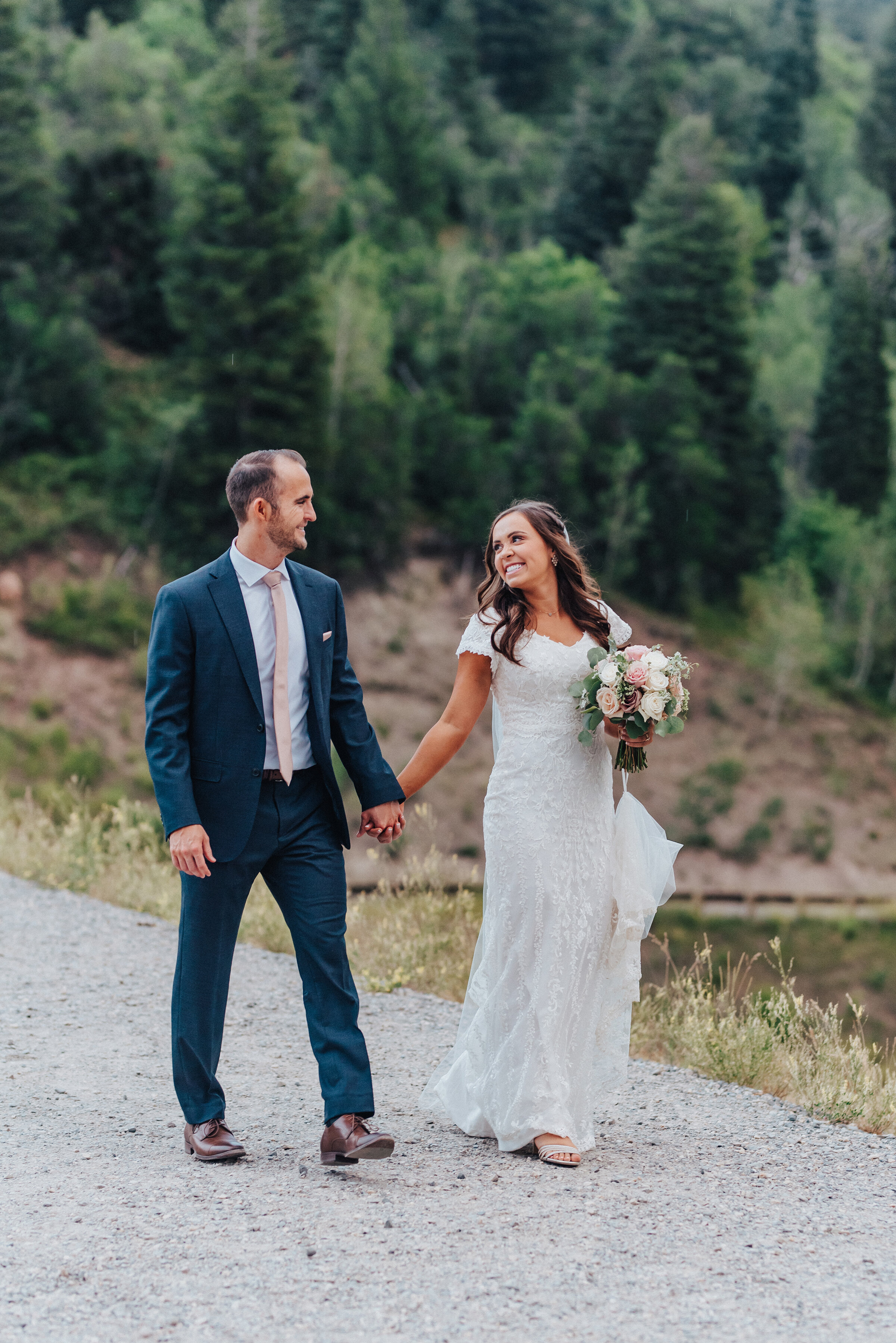 A smiling couple stroll down a paved pathway that surrounds the Tibble Fork Reservoir in American Fork canyon while holding hands. Navy suit light pink tie light pink floral bouquet exchanging glances evergreen trees #husbandandwife #younglove #tibbleforkreservoir #utahwedding #americanforkcanyon #coupleshoot #formals #weddingphotography #couplesgoals #couplephotography #weddingphotographer #couplesphotography #groom #bride