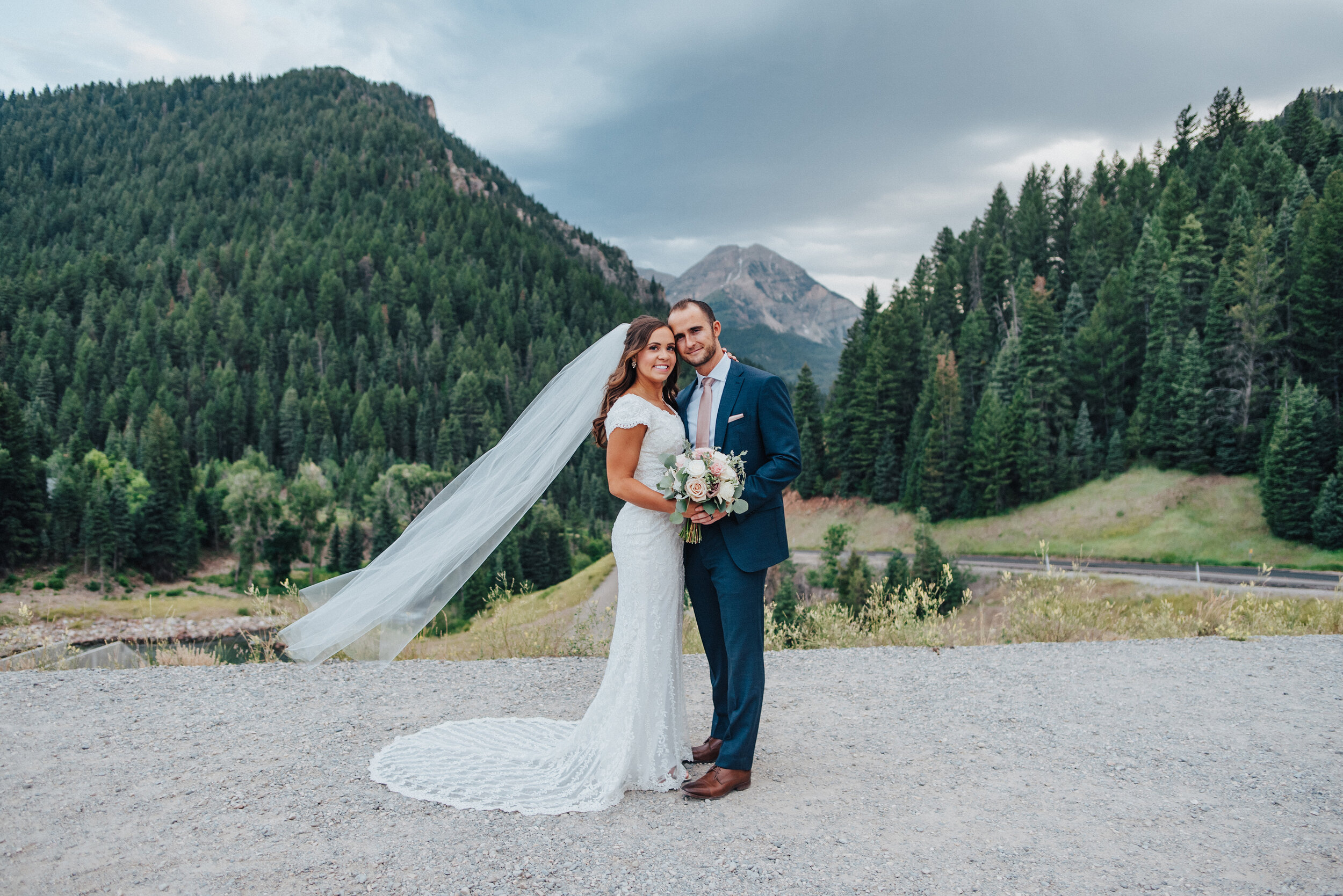 A gorgeous bride and groom look into the camera while softly embracing each other in front of the breathtaking Tibble Fork Reservoir. Navy suit light pink tie light pink floral bouquet evergreen trees mountains in the background classic wedding shot #husbandandwife #younglove #tibbleforkreservoir #utahwedding #americanforkcanyon #coupleshoot #formals #weddingphotography #couplesgoals #couplephotography #weddingphotographer #couplesphotography #groom #bride