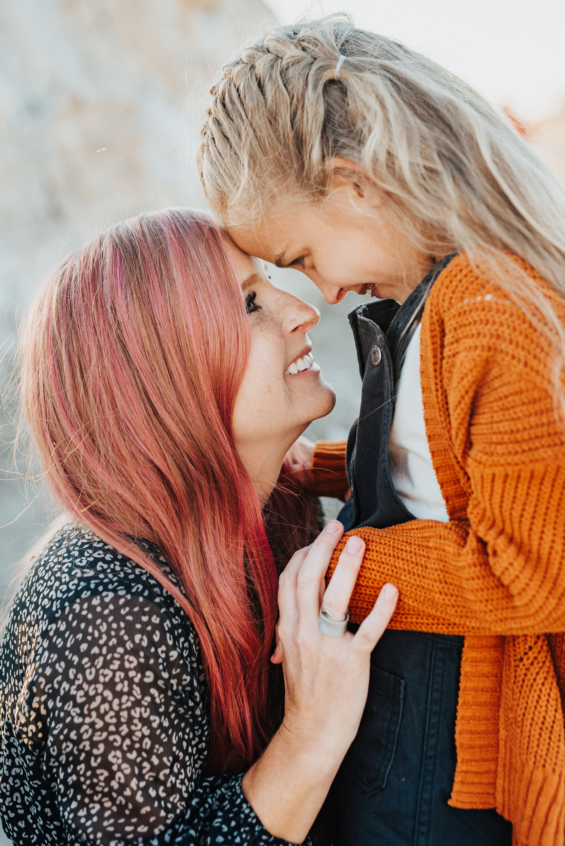 A beautiful mother and daughter share a sweet moment in a unique family photo shoot by Kristi Alyse Photography. Mother and daughter pose inspiration ideas and goals braided hair pink hair mother and daughter outfit inspiration ideas and goals family picture goals girl outfit inspiration perfect for fall photo shoots fall women outfit inspiration  #familypictures #utahphotographer #antelopeisland #outfitinspo #familypics #familyphotographer #pinkhair #saltlakecityphotog #slcfamilypictures