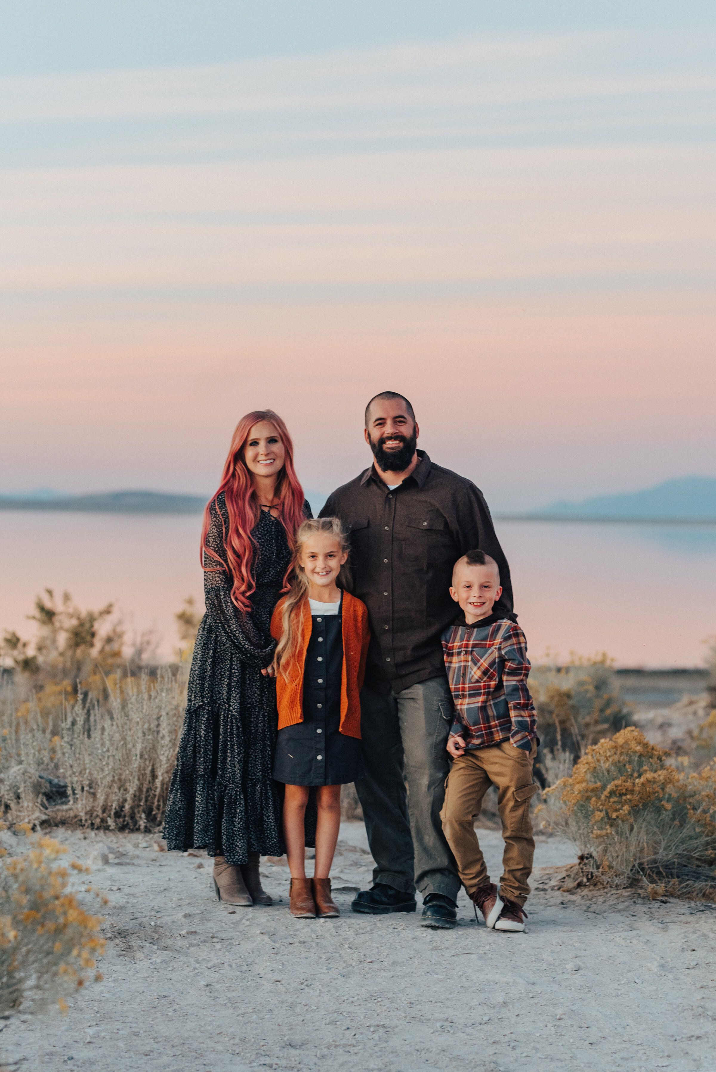 A beautiful family standing on Antelope Island beach at sun set in a professional photo shoot by Kristi Alyse Photography. Family goals fall client attire inspiration family pose inspiration ideas and goals unique family photo shoot pink hair and a pho hawk fall outdoor photo shoot goals professional Utah Photographer #familypictures #utahphotographer #antelopeisland #outfitinspo #familypics #familyphotographer #pinkhair #saltlakecityphotog #slcfamilypictures