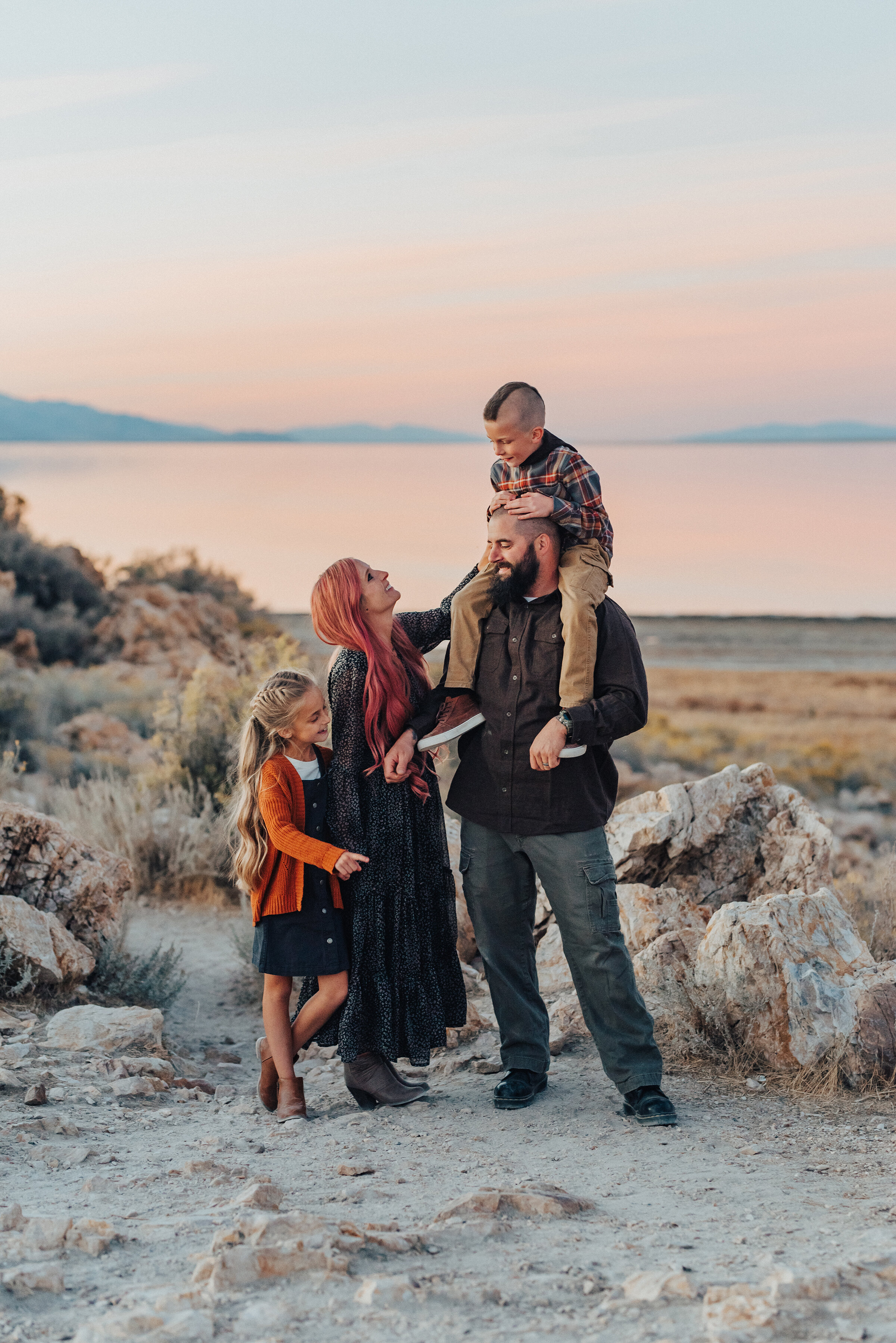 A mother and daughter look up at father and son in a beautiful warm fall family photo shoot by professional photographer Kristi Alyse Photography. Sunset goals family pose inspiration fun and playful family photo shoot SLC photographer Antelope Island couple and family goals unique family pose inspiration  #familypictures #utahphotographer #antelopeisland #outfitinspo #familypics #familyphotographer #pinkhair #saltlakecityphotog #slcfamilypictures