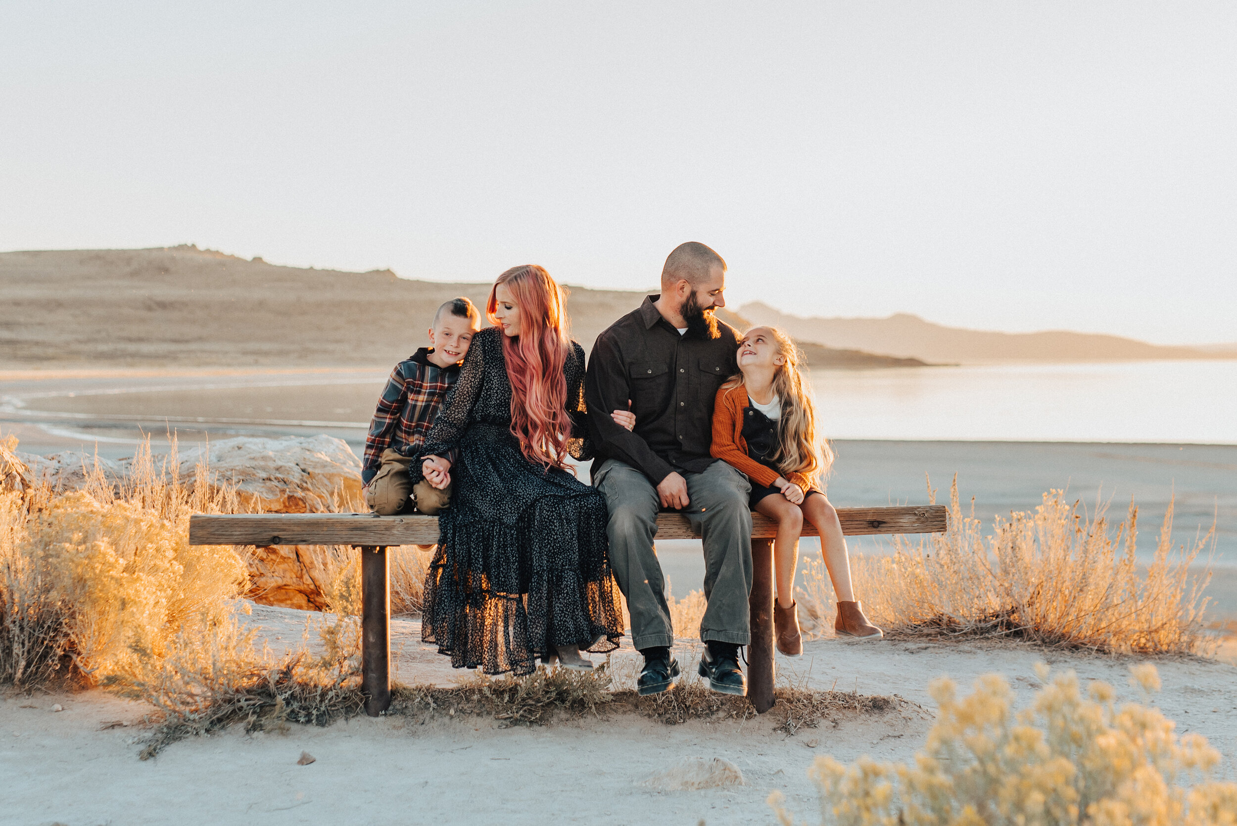 A glowing family sitting together in a beautiful sun set photo shoot by Kristi Alyse Photography. Utah photographer goals ideas and inspiration Antelope Island photo shoot goals young family photo shoot inspiration sitting family pose inspiration love this family moment fall goals professional photographer goals #familypictures #utahphotographer #antelopeisland #outfitinspo #familypics #familyphotographer #pinkhair #saltlakecityphotog #slcfamilypictures