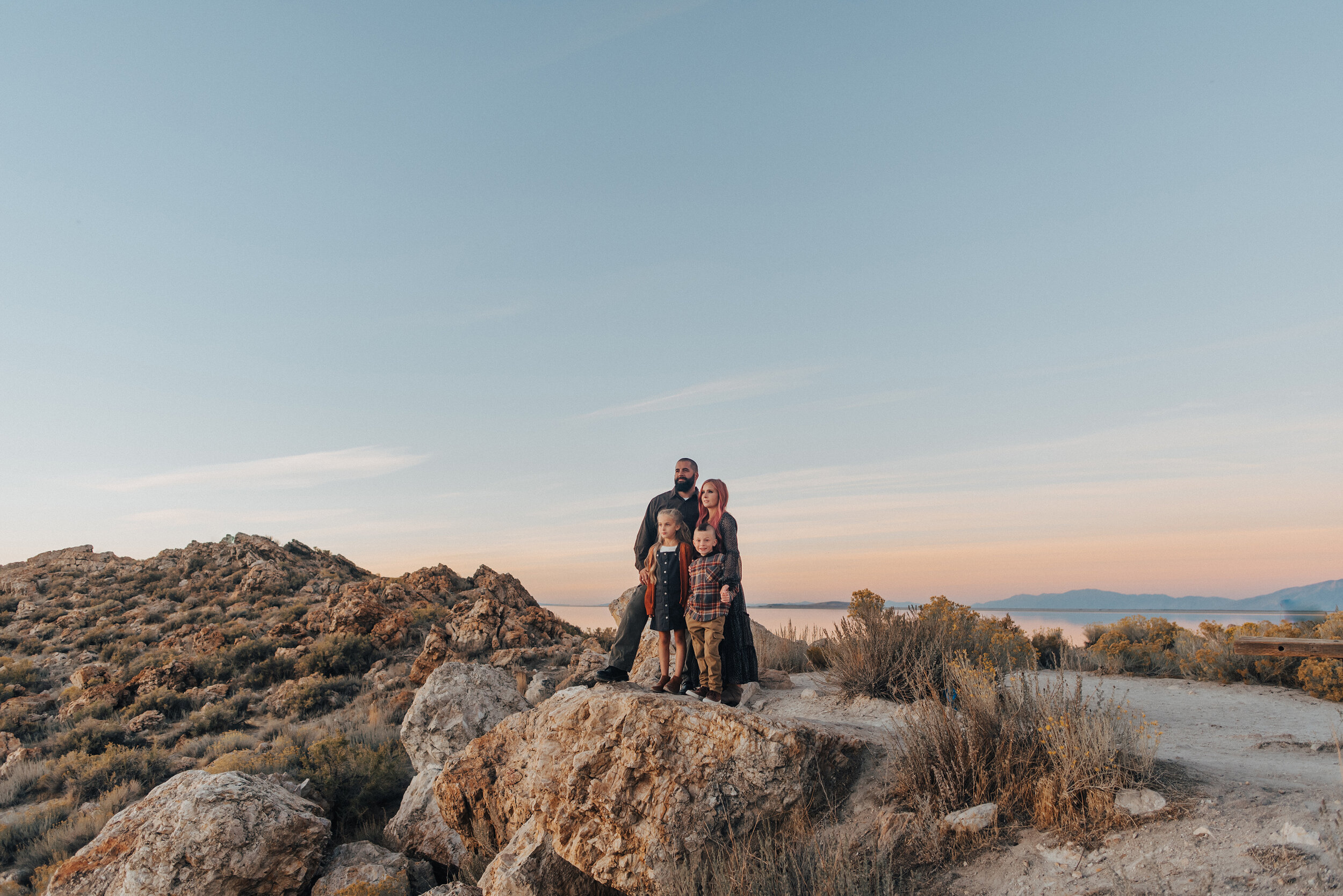 A stunning family stares into the distance in a beautiful sunset family photo shoot in Syracuse Utah's Antelope Island. Family pose goals young family photo shoot inspiration family attire inspiration ideas and goals  pink hair goals professional Utah photographer Kristi Alyse Photography standing on rocks family pose inspiration #familypictures #utahphotographer #antelopeisland #outfitinspo #familypics #familyphotographer #pinkhair #saltlakecityphotog #slcfamilypictures