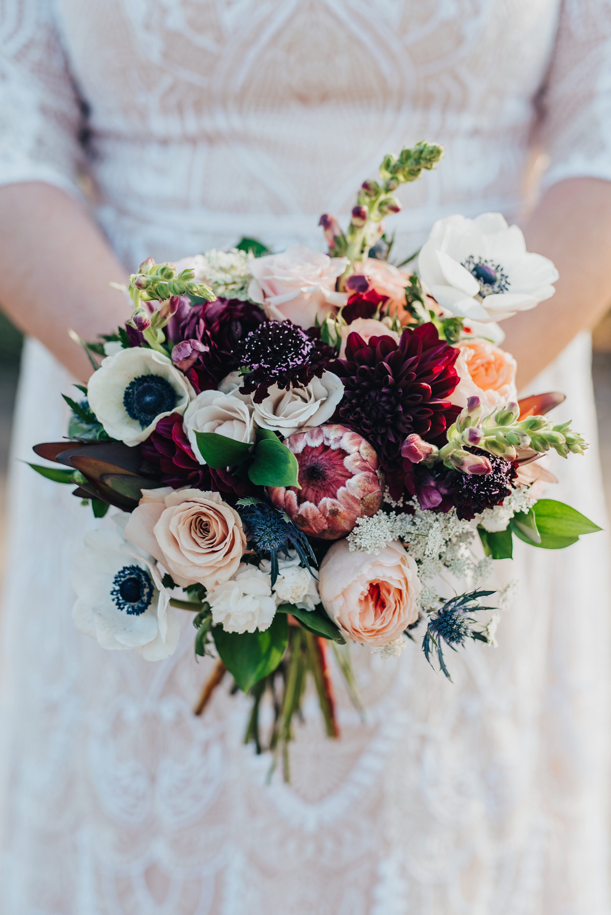 Stunningly detailed shot of the gorgeous brides flower bouquet in Logan, Utah by Kristi Alyse Photography. Brides bouquet of colorful flowers inspo wedding day floral arrangement lace wedding dress meaningful details unique photography northern Logan Utah wedding day bridals #weddinginspo #loganutah #brideandgroom #utahbride#utahweddingphotographer #meaningfulmoment #weddingphotography #northernutahwedding #weddinghairstyles #weddingday #bridals