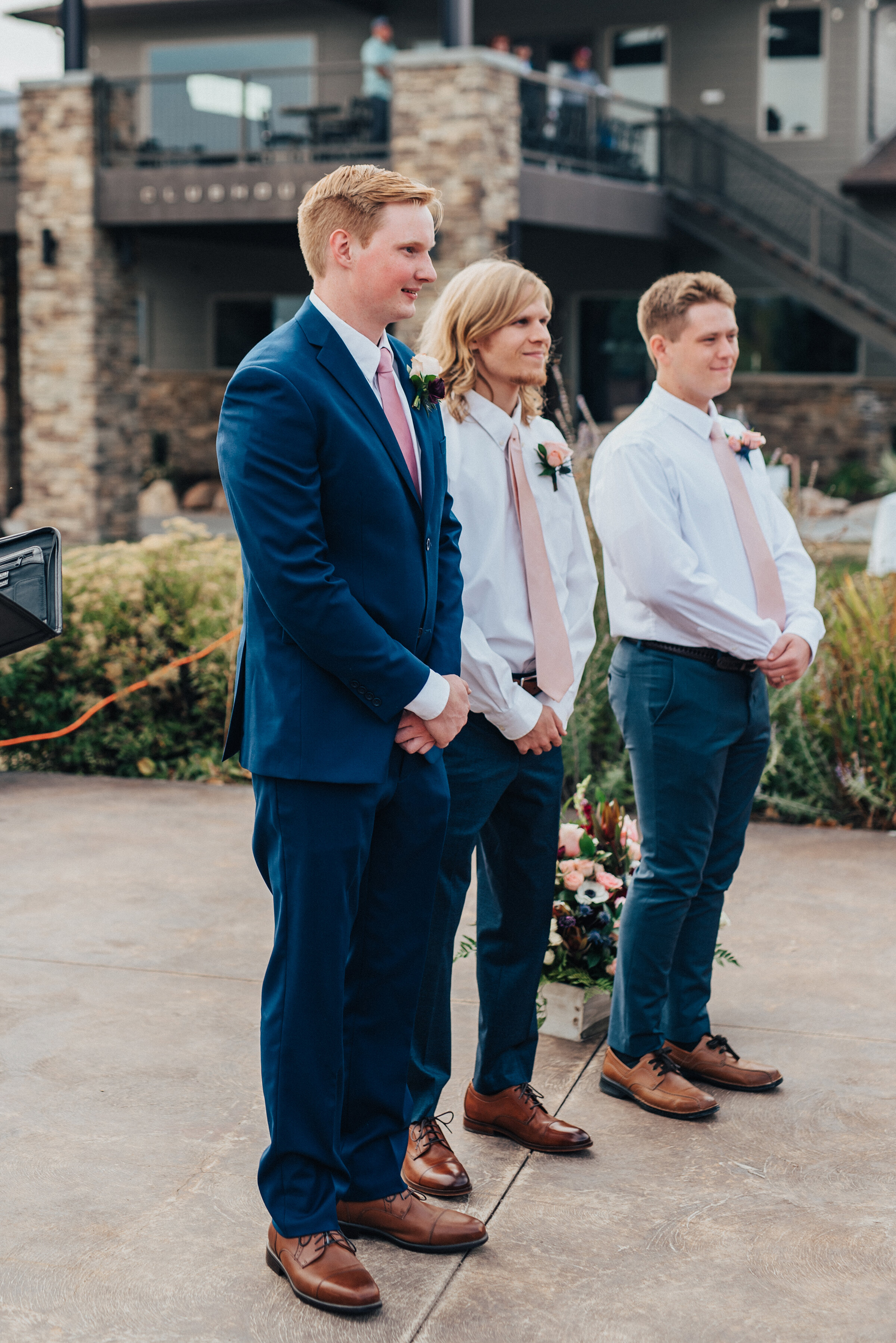 Handsome shot of the groom and groomsmen awaiting the ceremony in Logan, Utah captured by Kristi Alyse Photography. Groomsmen line wedding day blue suits pink tie wedding ceremony in northern Utah quality moments photography grooms boutonnieres best man Utah wedding #weddinginspo #loganutah #brideandgroom #utahbride#utahweddingphotographer #meaningfulmoment #weddingphotography #northernutahwedding #weddinghairstyles #weddingday #bridals