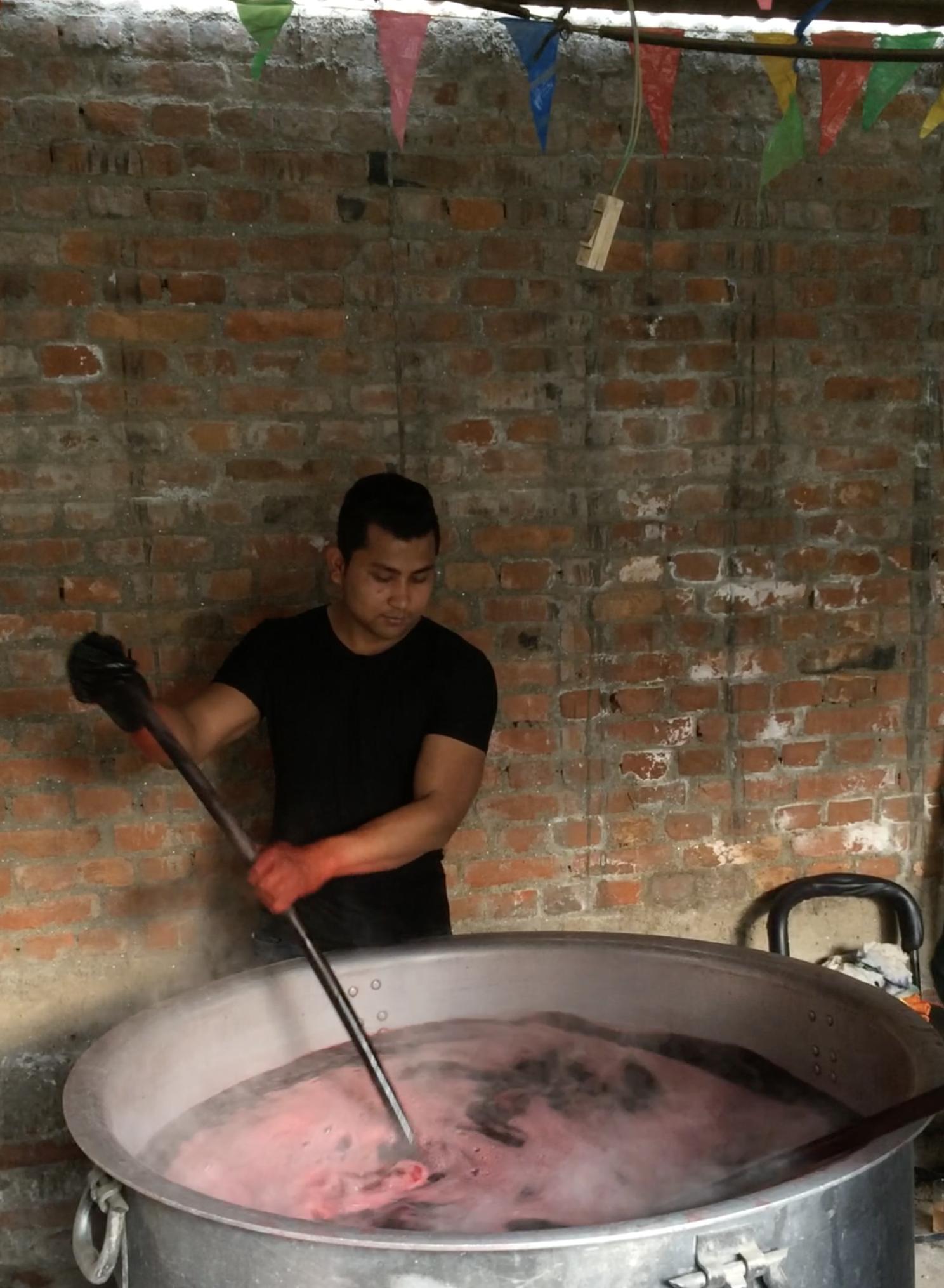 Stirring the yarn in a steaming dye bath