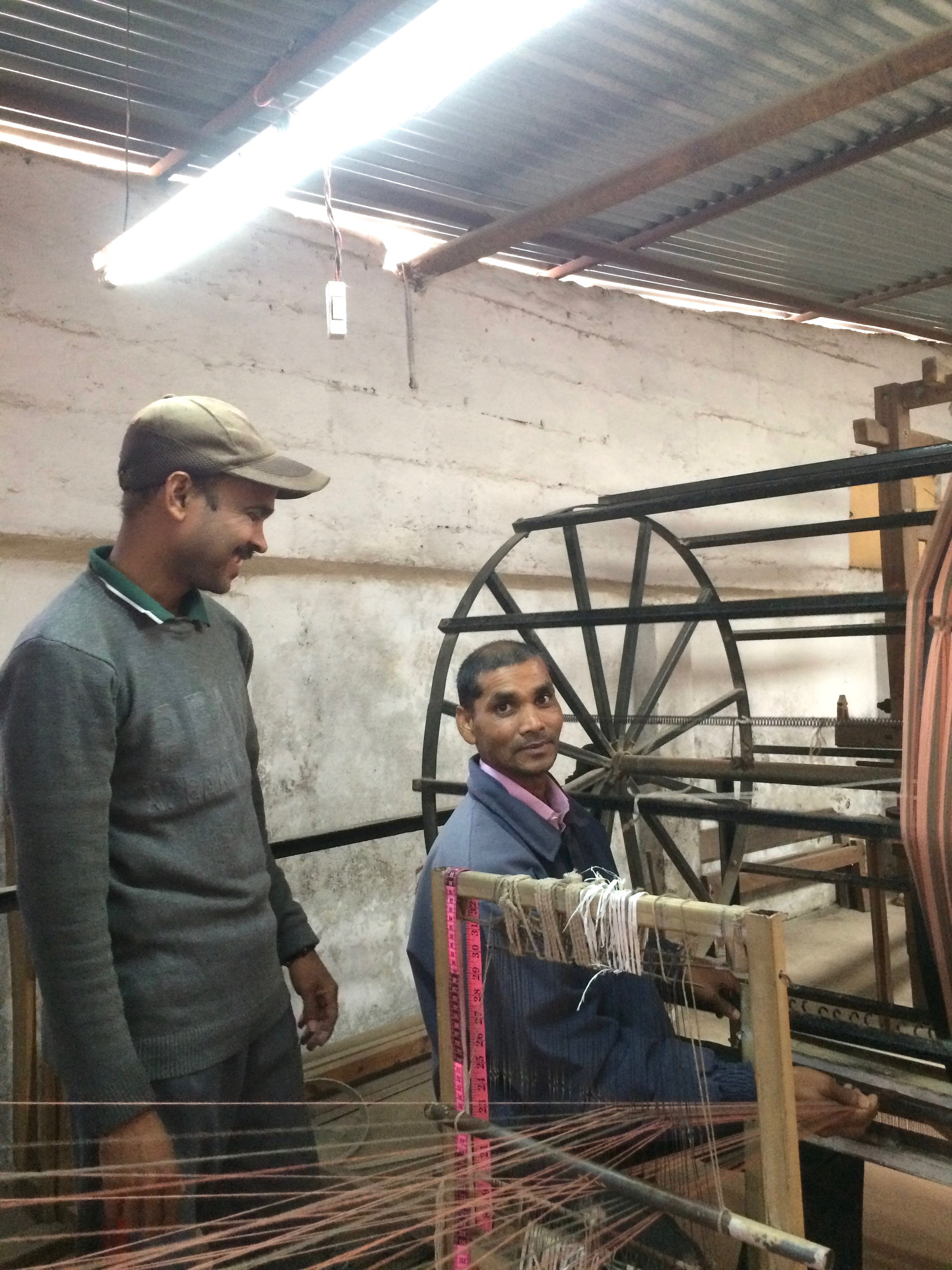In this photo, Kisor (seated) and Padam share a light moment while preparing the warp.