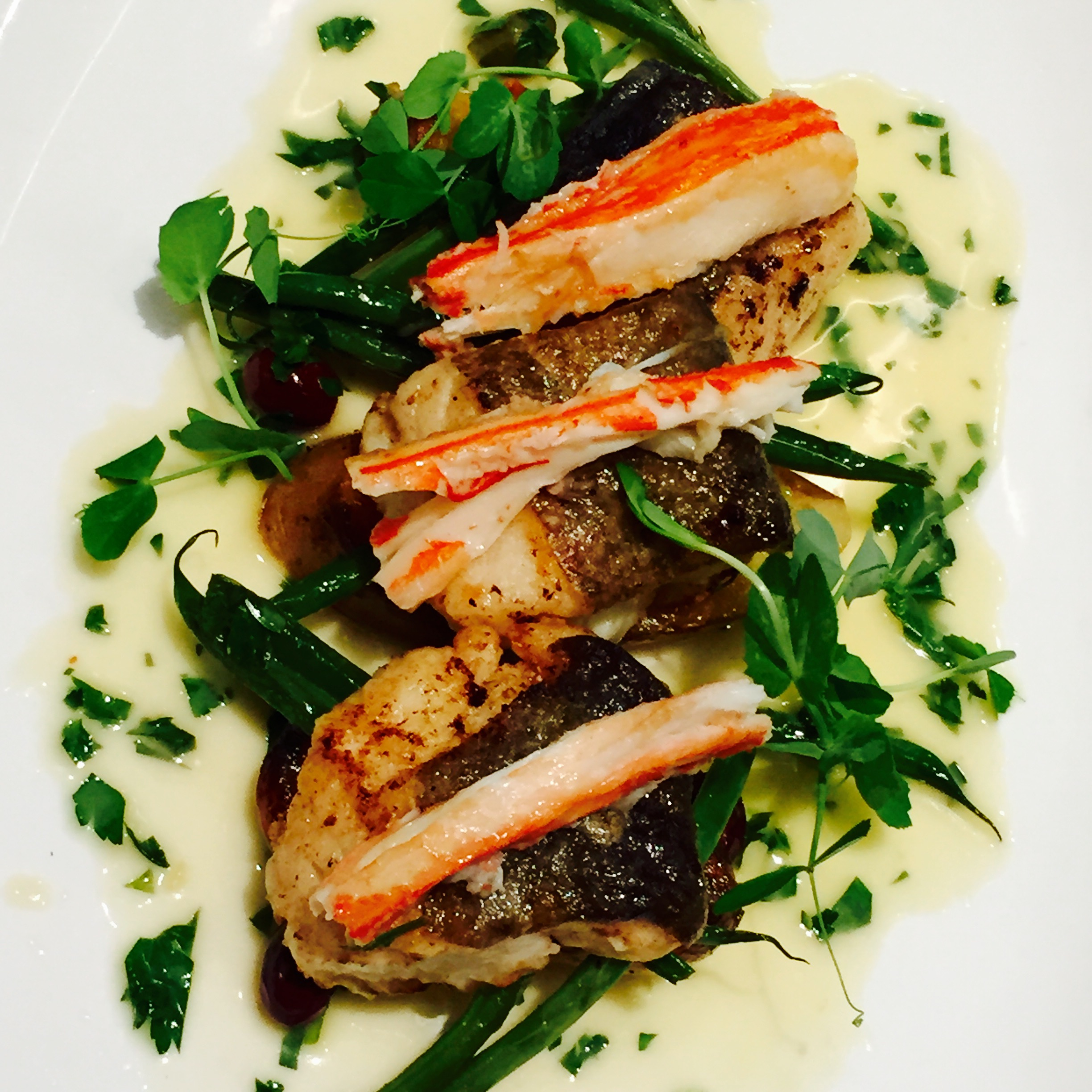 Seared Seabass with perfectly poached King Crab Legs in a rich herb butter sauce.