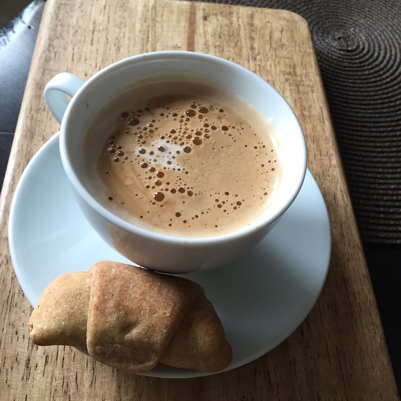A perfect latte with a homemade black olive croissant.