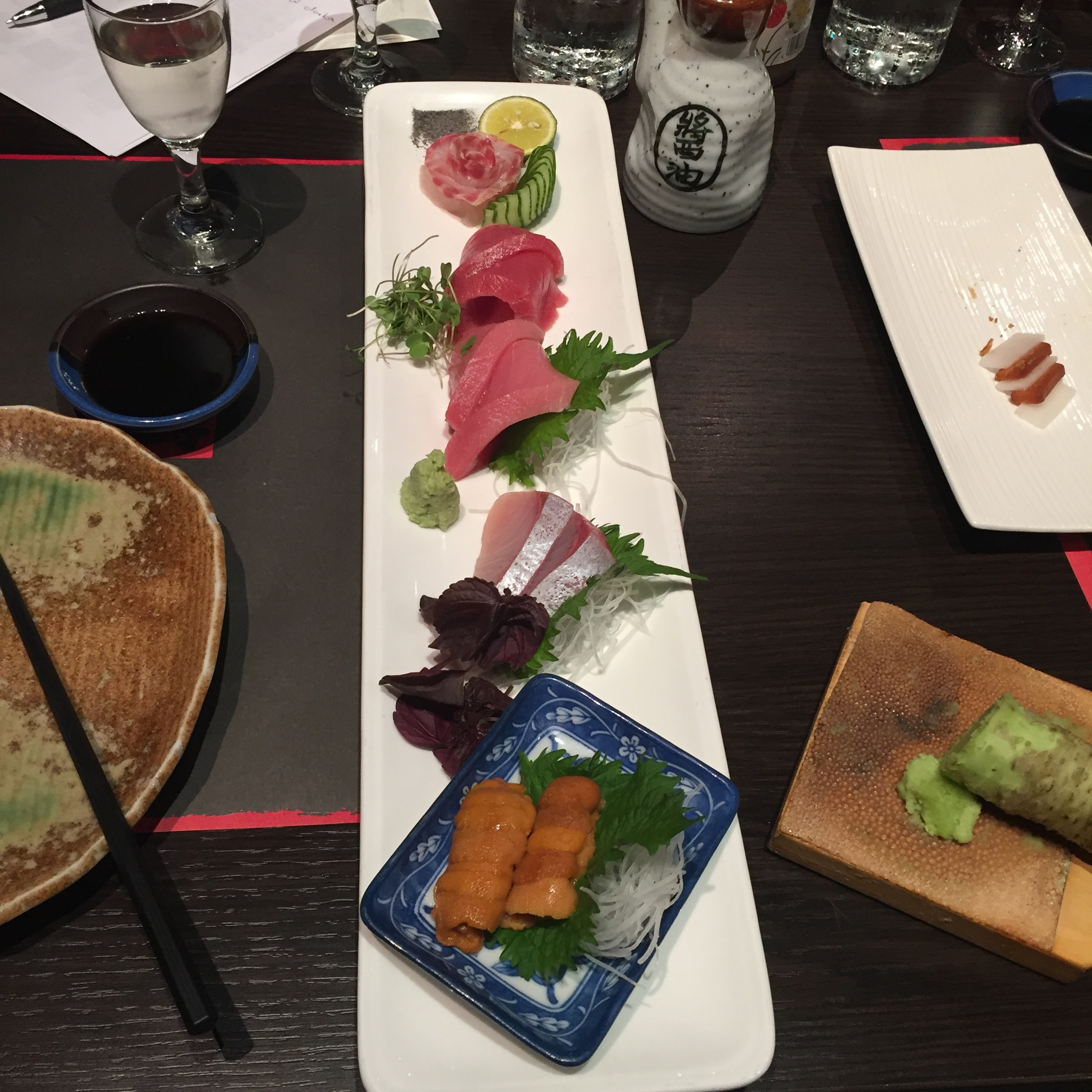 From front to back; Gold Fluke with sour plum and gold leaf Truffle oil glazed salmon, Fatty Yellowtail, Torched Scallop, Blue Fin Tuna marinated in sake, Mirin and soy,Torched Fatty Tuna with spicy radish