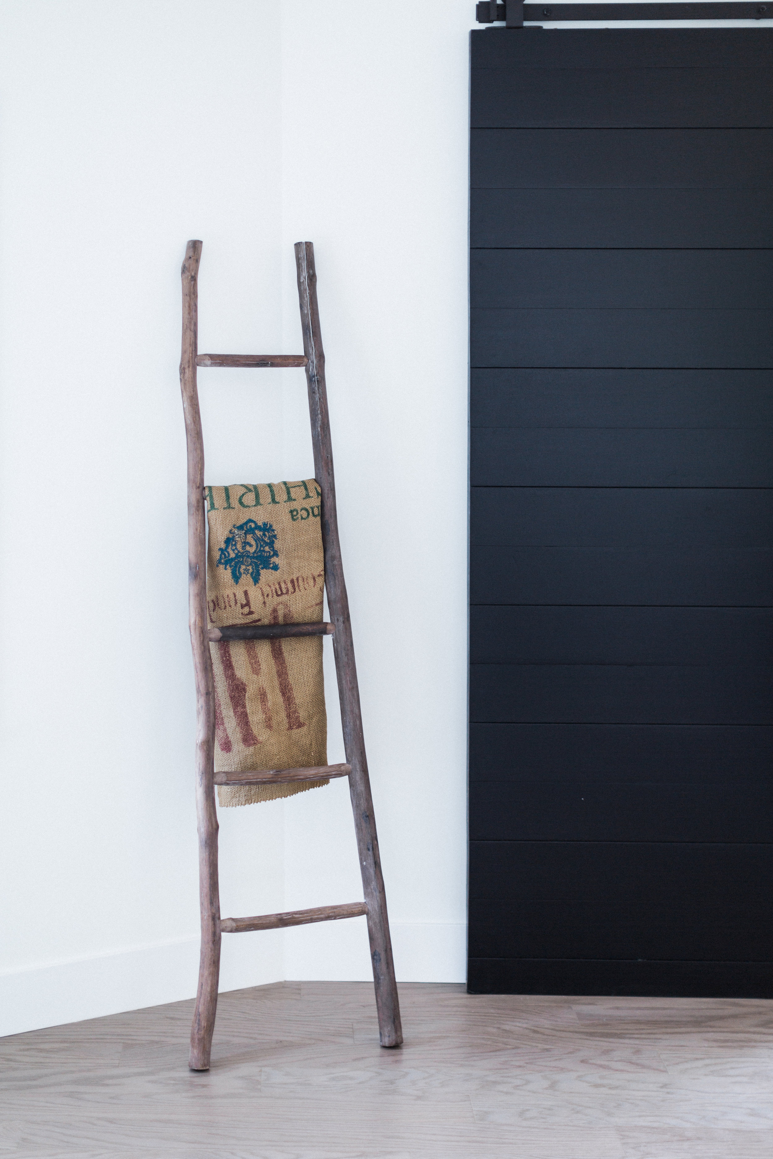 We'll move on to other rooms soon, but pretty please look at this rustic wood ladder next to the rad sliding barn door our client used. A burlap coffee sack is casually placed there as if by accident (riiiiiiiiggghhhht).