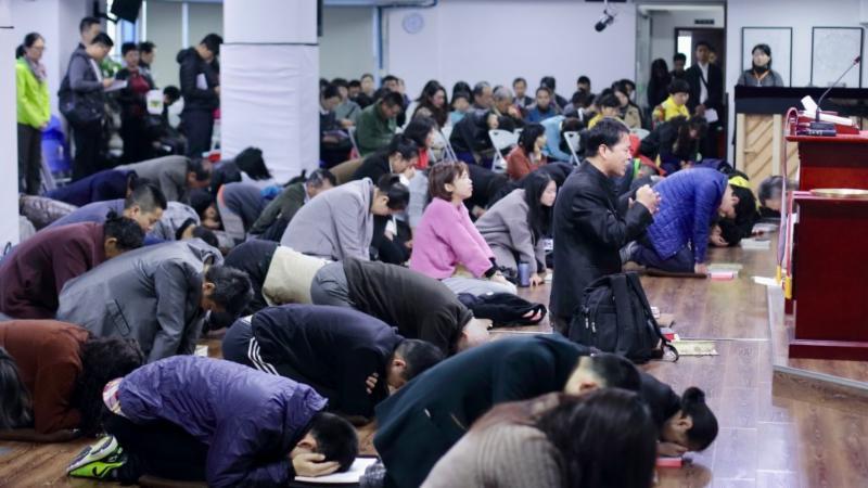 Membri della Early Rain Covenant Church di Chengdu (Cina) raccolti in preghiera.