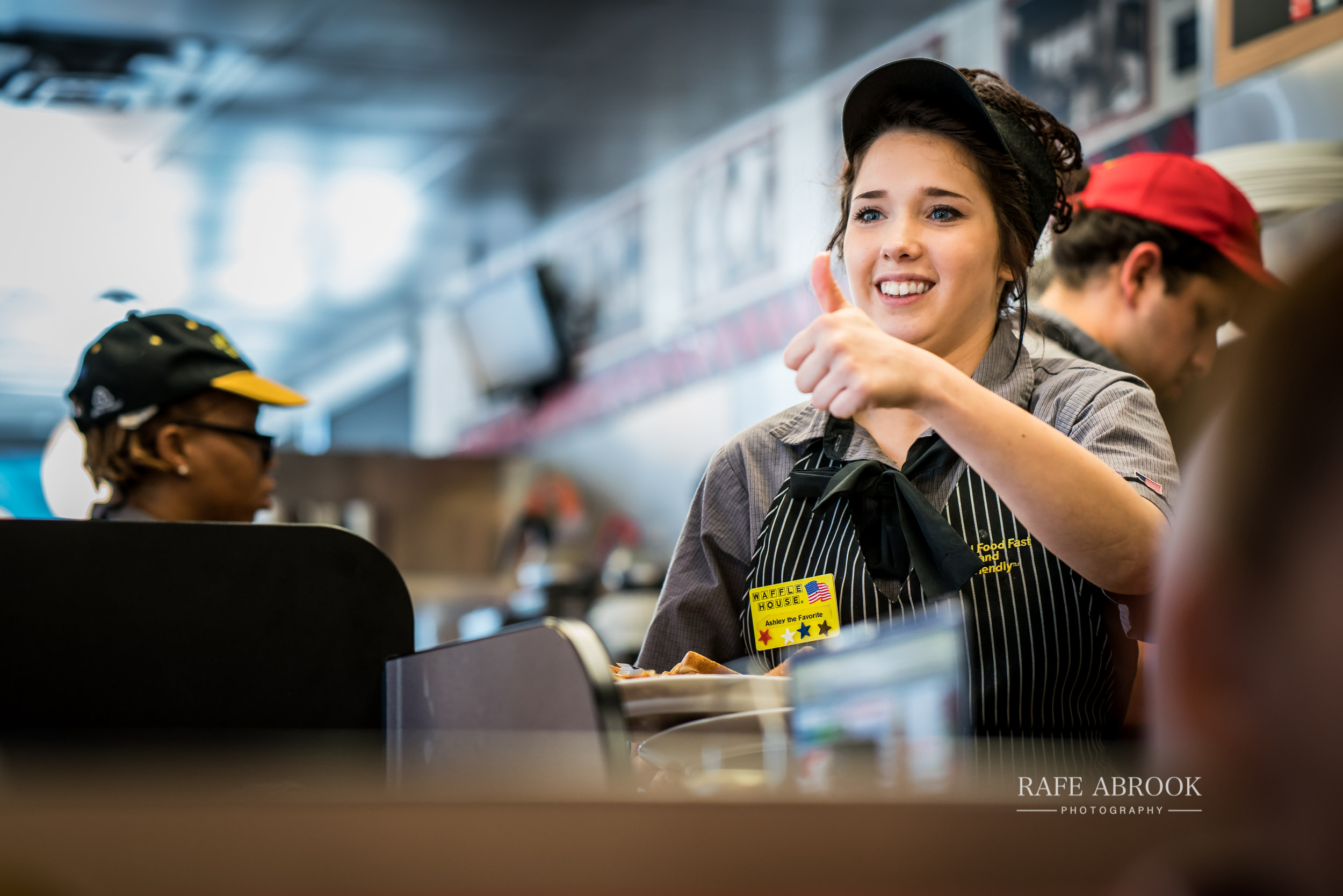 Service with an American style at The Waffle House. Presumably that customer she is signalling to didn't order the grits.