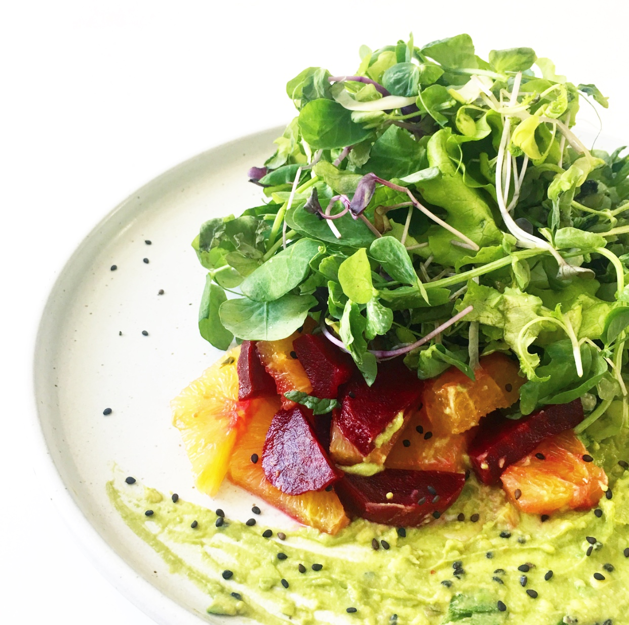 Tangles of local sprouts and greens piled high atop a beautiful medley of beetroot and citrus with a fiery avocado tahini herb dressing —#vegan has never tasted so good. Yum!