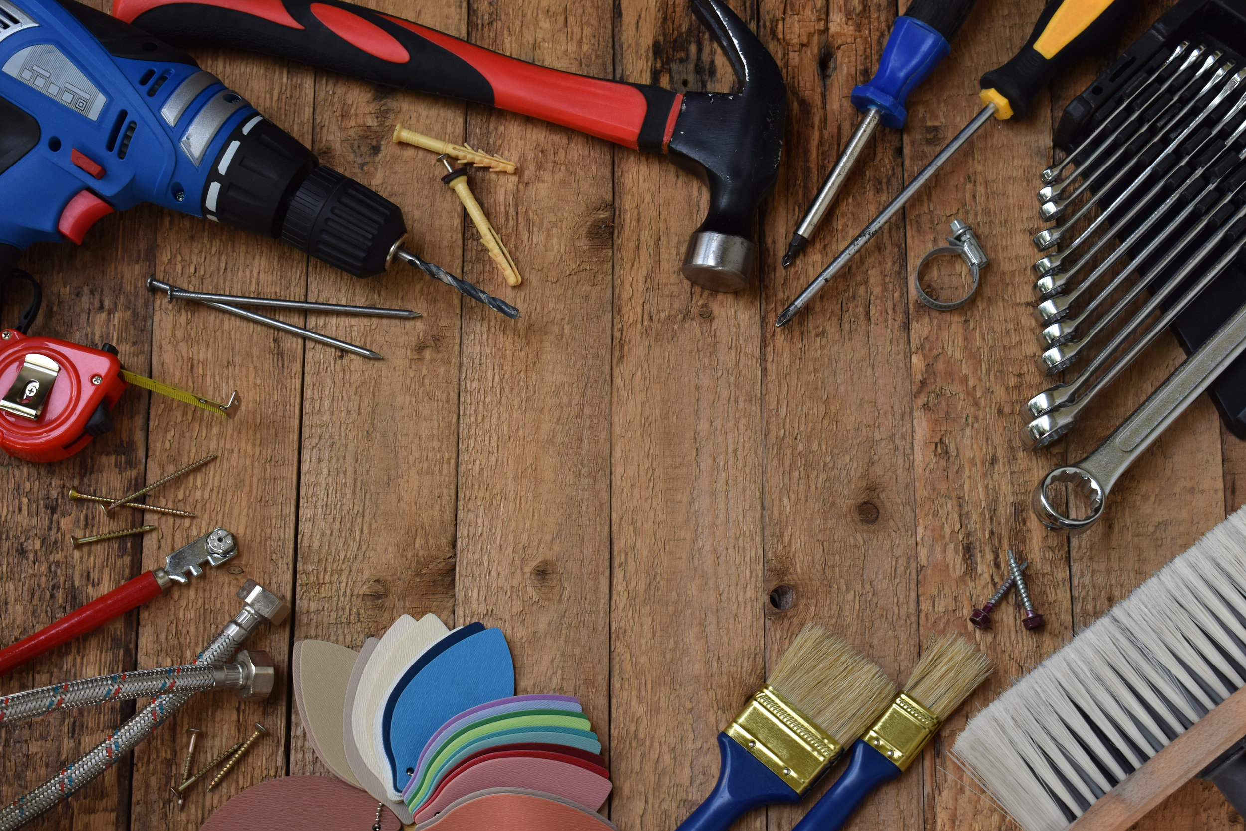 Set of tools for building and treatment on wooden background: hammer, measuring tape, drill.