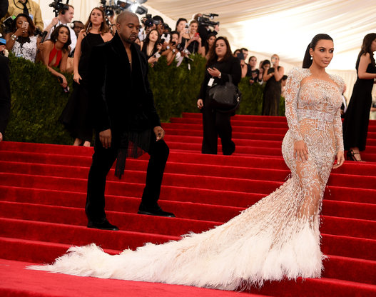The never smiling Kanye West watches wifey Kim Kardashian take the red carpet in Roberto Cavalli.