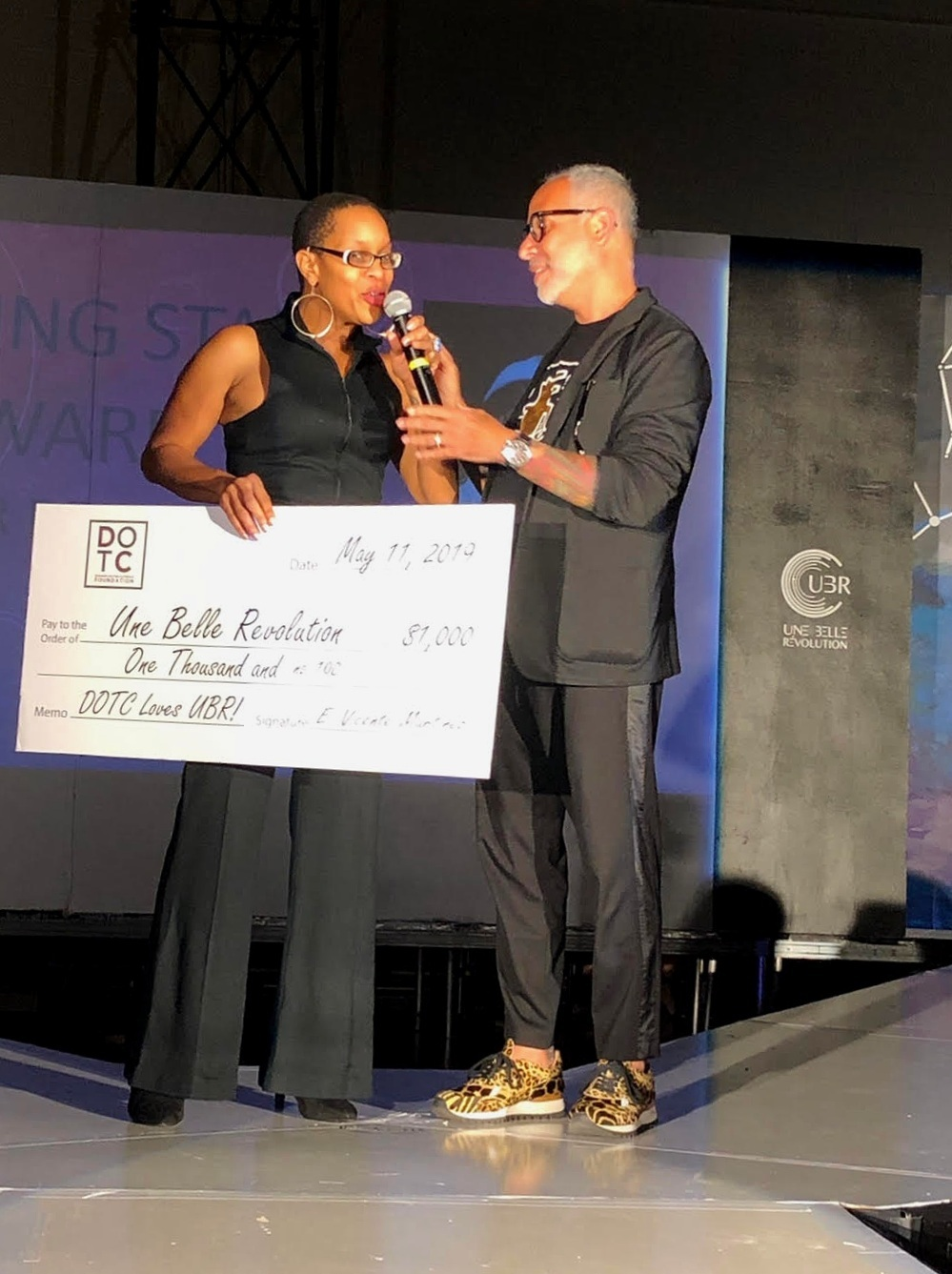 DOTC -  Doggies on the Catwalk  founder, E. Vincent Martinez presented Ms. Williams with a donation for her program. DOTC was created by Martinez in his Grady High School classroom 12 years ago and in alignment with the DOTC Foundation's mission of supporting arts programs and fashion schools, the SEAM Grant has been created. Une Belle Revolution is its first recipient.  SEAM - Supporting Education in Apparel Mastery .
