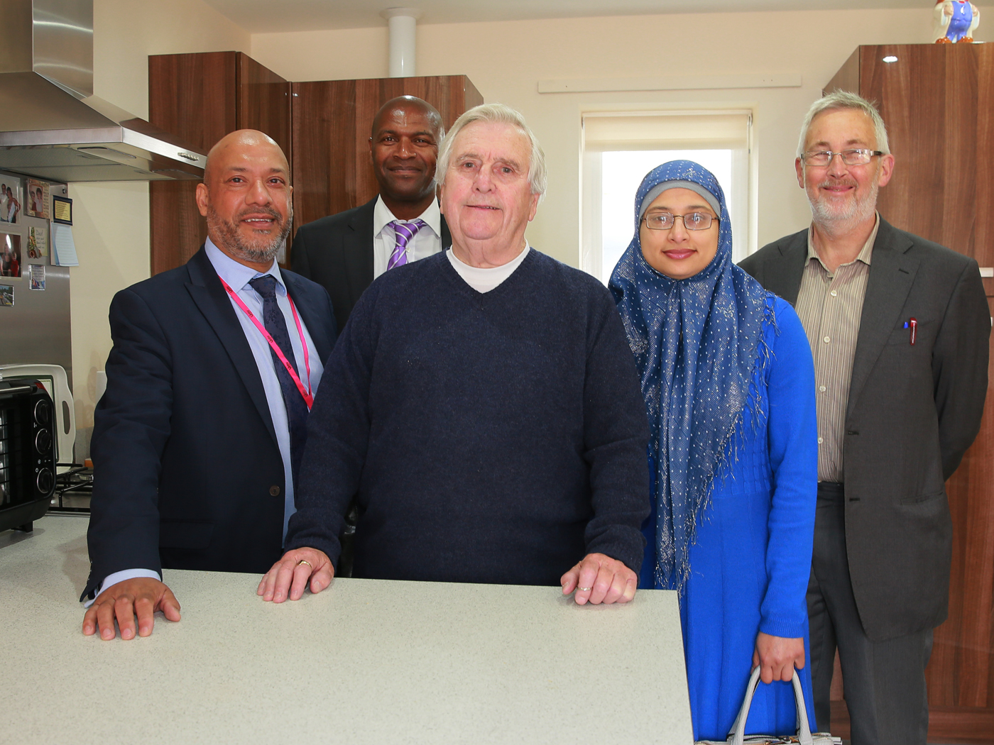 Ray Smith (centre) pictured in his new Stratford Court property with (from left to right) Unity's chief executive Ali Akbor, director of regeneration Wayne Noteman, board member   Shazia   Khan and   Leeds City Council  's   executive member for regeneration, transport and planning   Cllr Richard Lewis