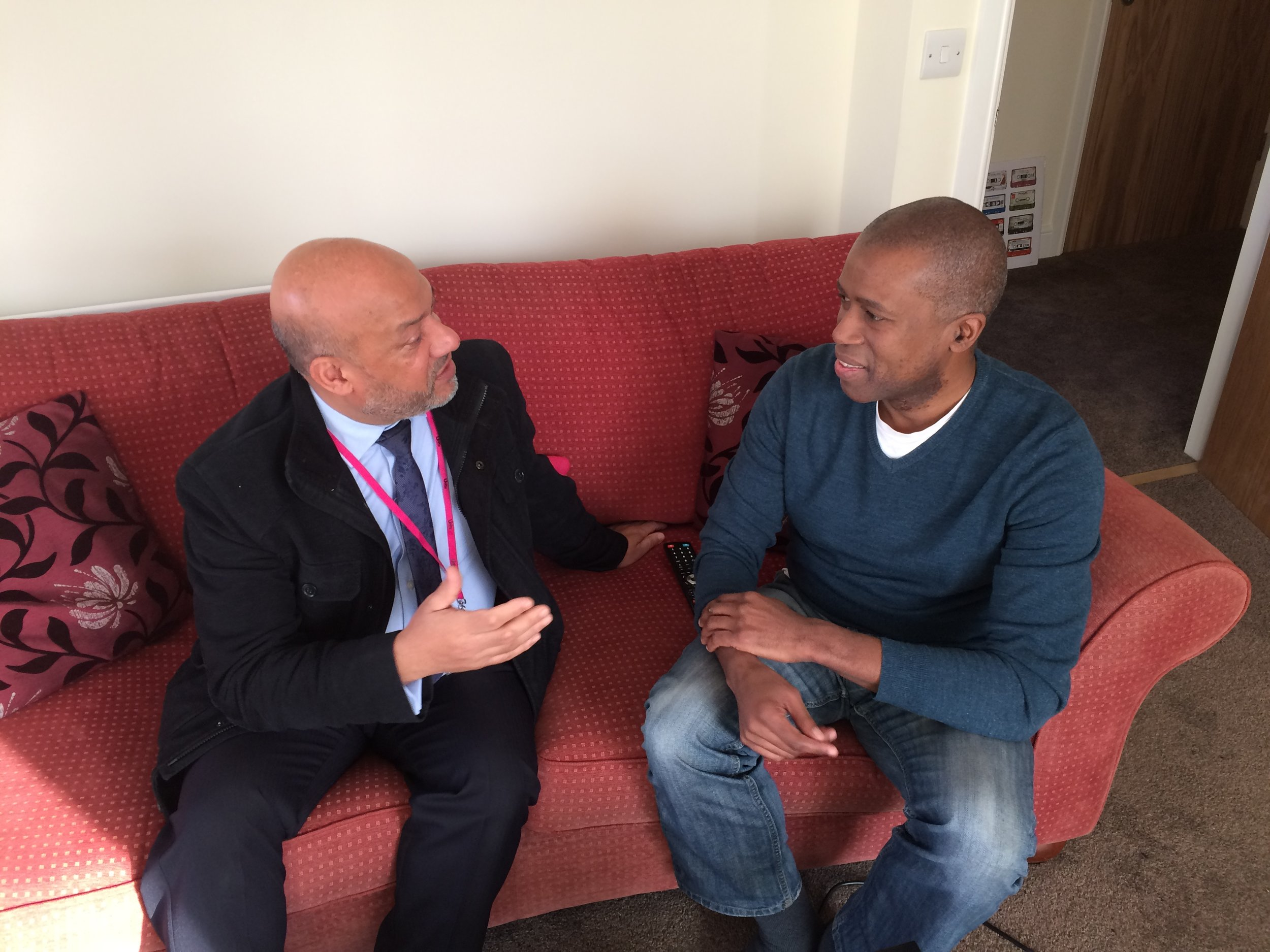 Holborn Court tenant Ian Bailey (right) chats to Unity chief executive Ali Akbor in the living room of his new property in Little London