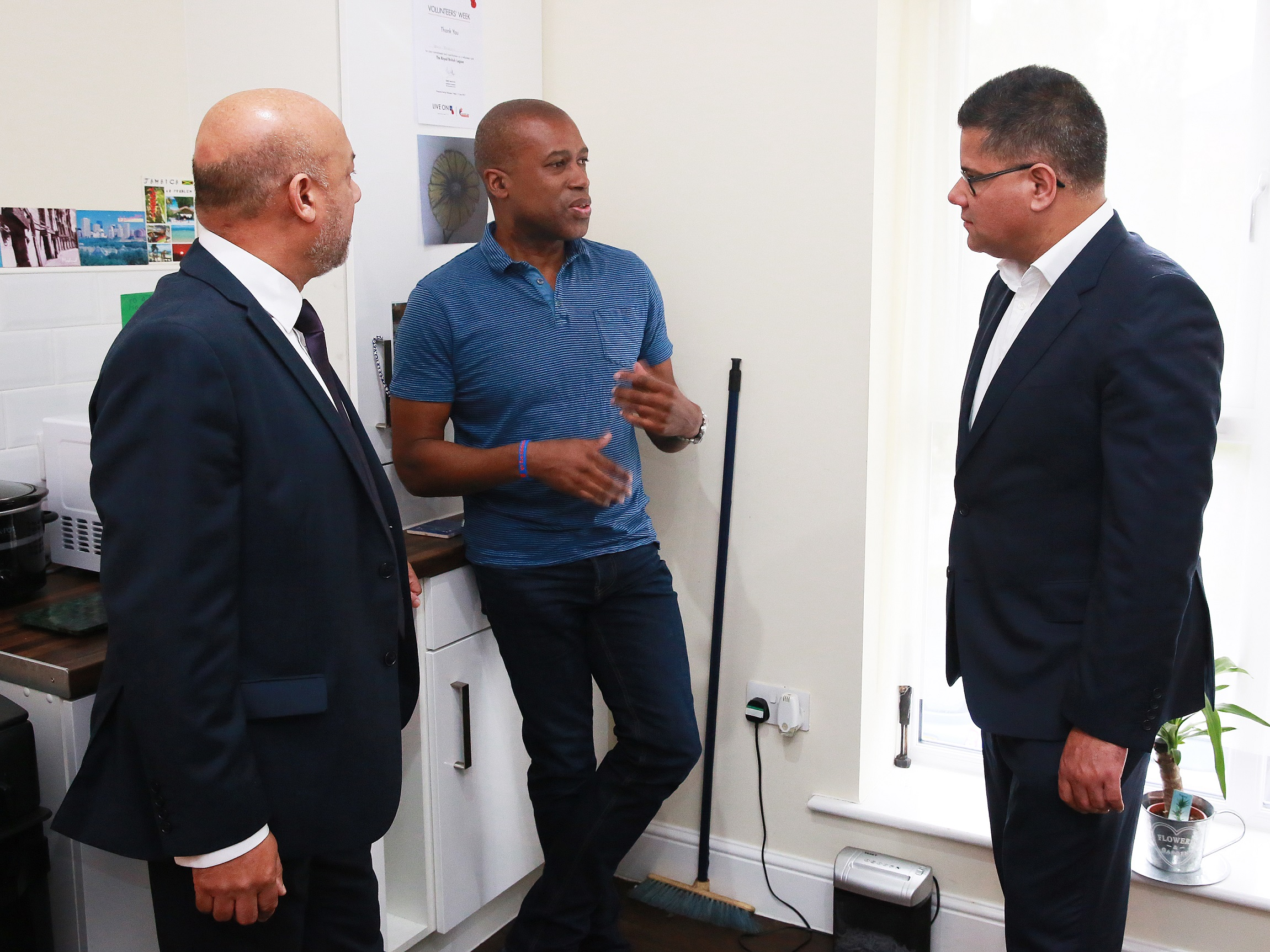 Holborn Court resident Ian Bailey (centre) welcomes Housing and Planning Minister Alok Sharma (right) and Unity chief executive Ali Akbor (left) into his new home at Holborn Court in Little London, Leeds.