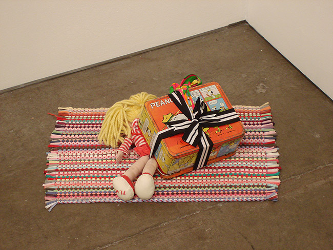 """Untitled (little bitch)""  (2007)  Rug, lunch box doll  23 x 14 x 7 in"