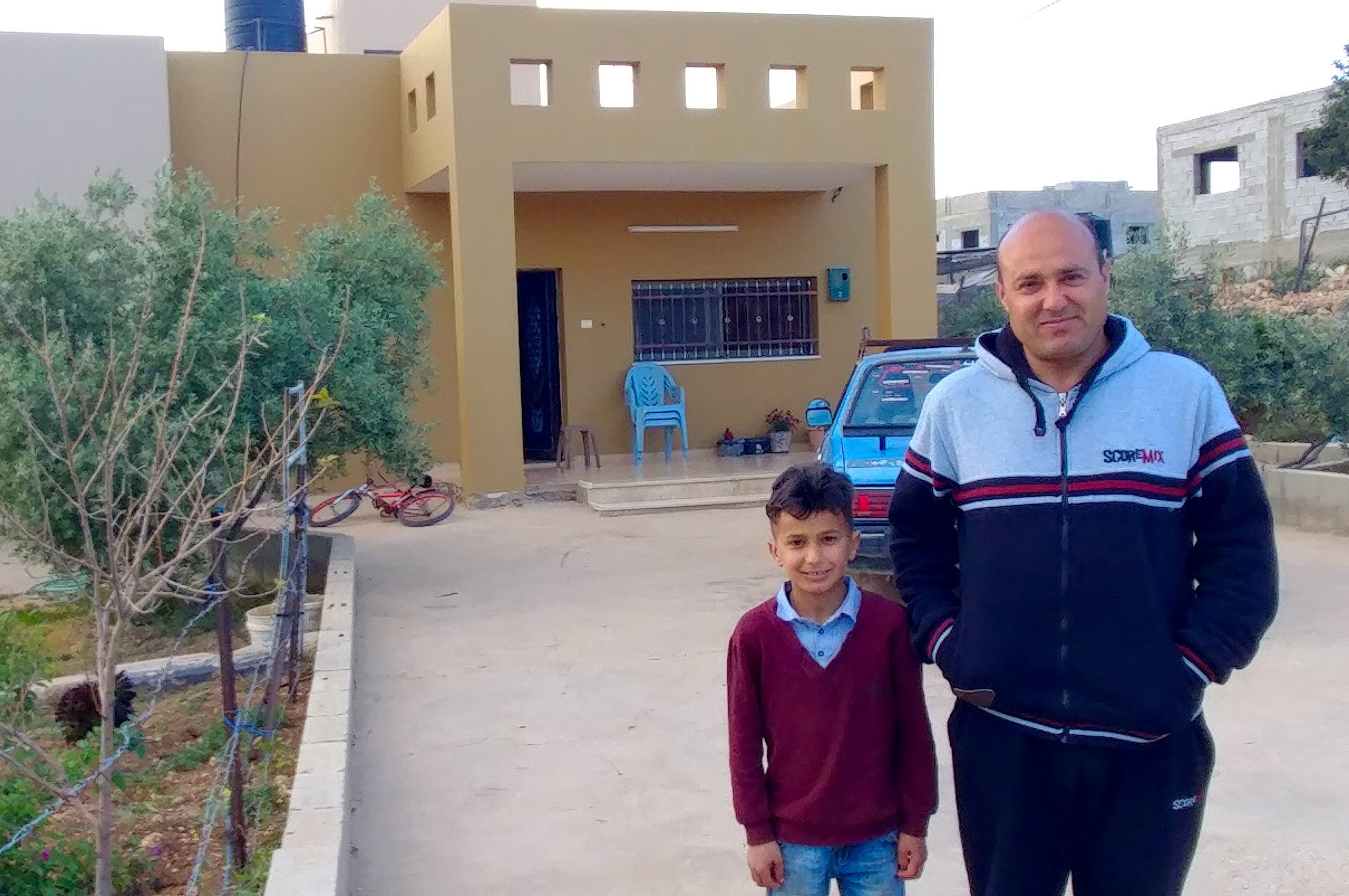 Shady and his father in front of their home