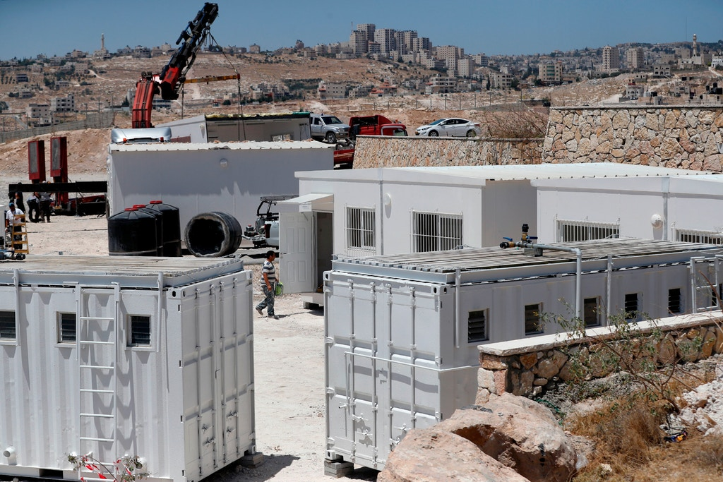 Israeli workers place container houses near the town of Al-Eizariyah in the occupied West Bank on July 9, 2018, to absorb residents of the Palestinian Bedouin village of Khan al-Ahmar, who are set to be evicted. Photo: Ahmad Gharabli/AFP/Getty Images