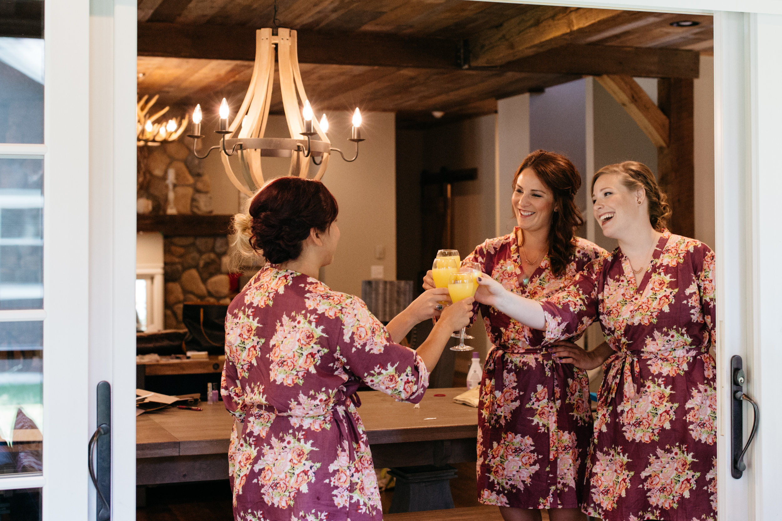 Bridesmaids wearing floral print robes drinking mimosas in northern Minnesota cabin on Gull Lake. Wedding photography by Britt DeZeeuw, Grand View Lodge wedding photographer.