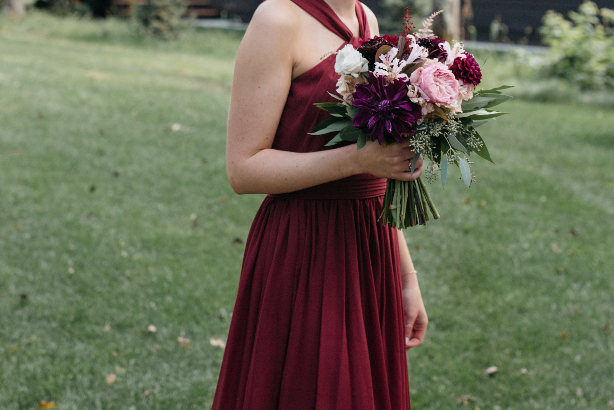 Purple flower bouquet by Bloom Designs and crimson bridesmaid dress at Grand View Lodge. Wedding Photography by Britt DeZeeuw.