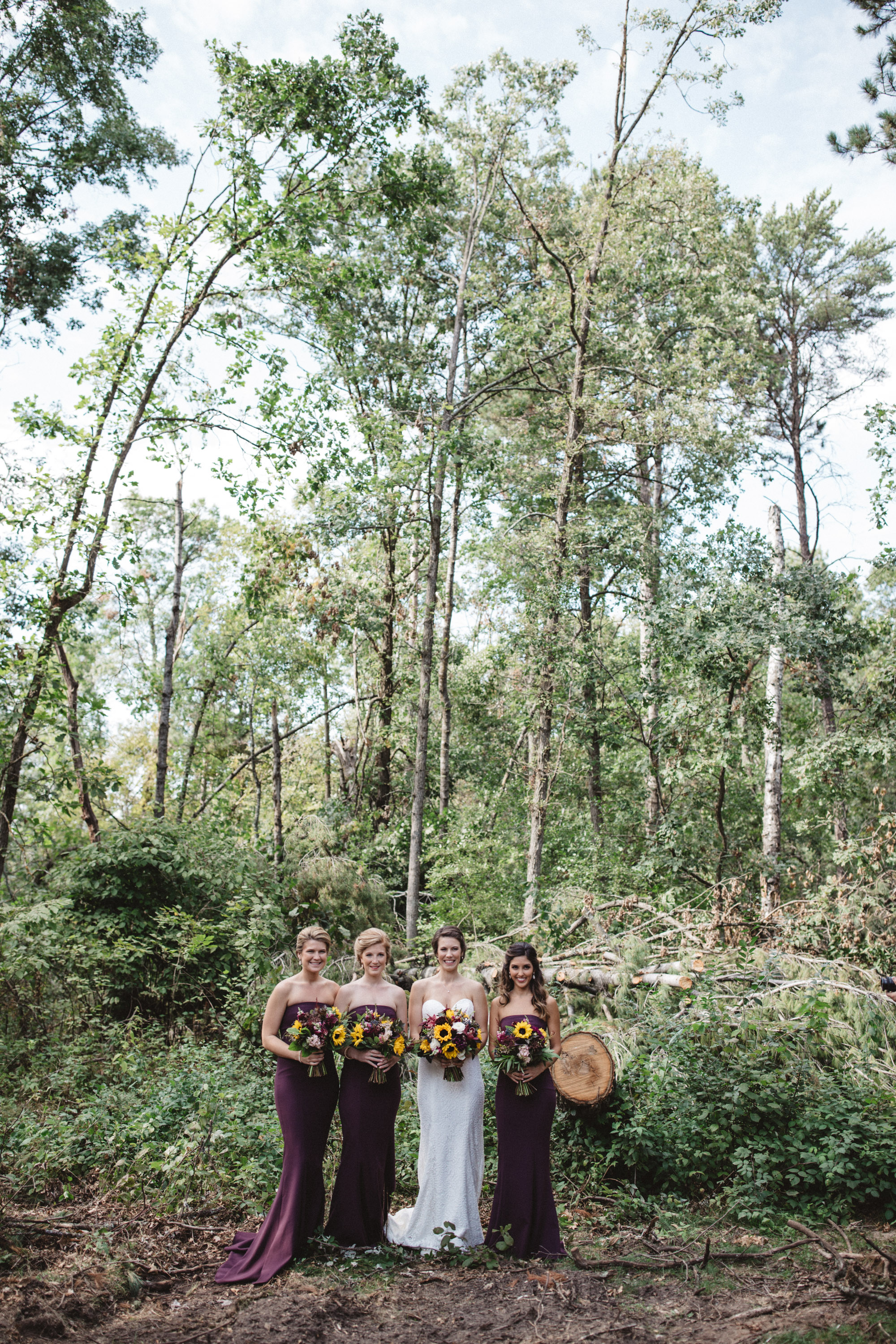Bride and bridesmaids in the woods at Grand View lodge in Northern Minnesota. Wedding photography by Britt DeZeeuw, Brainerd photographer.