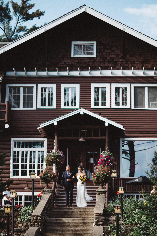 Bride walking down grand staircase at Grand View Lodge. Photography by Britt DeZeeuw, Brainerd MN wedding photographer.