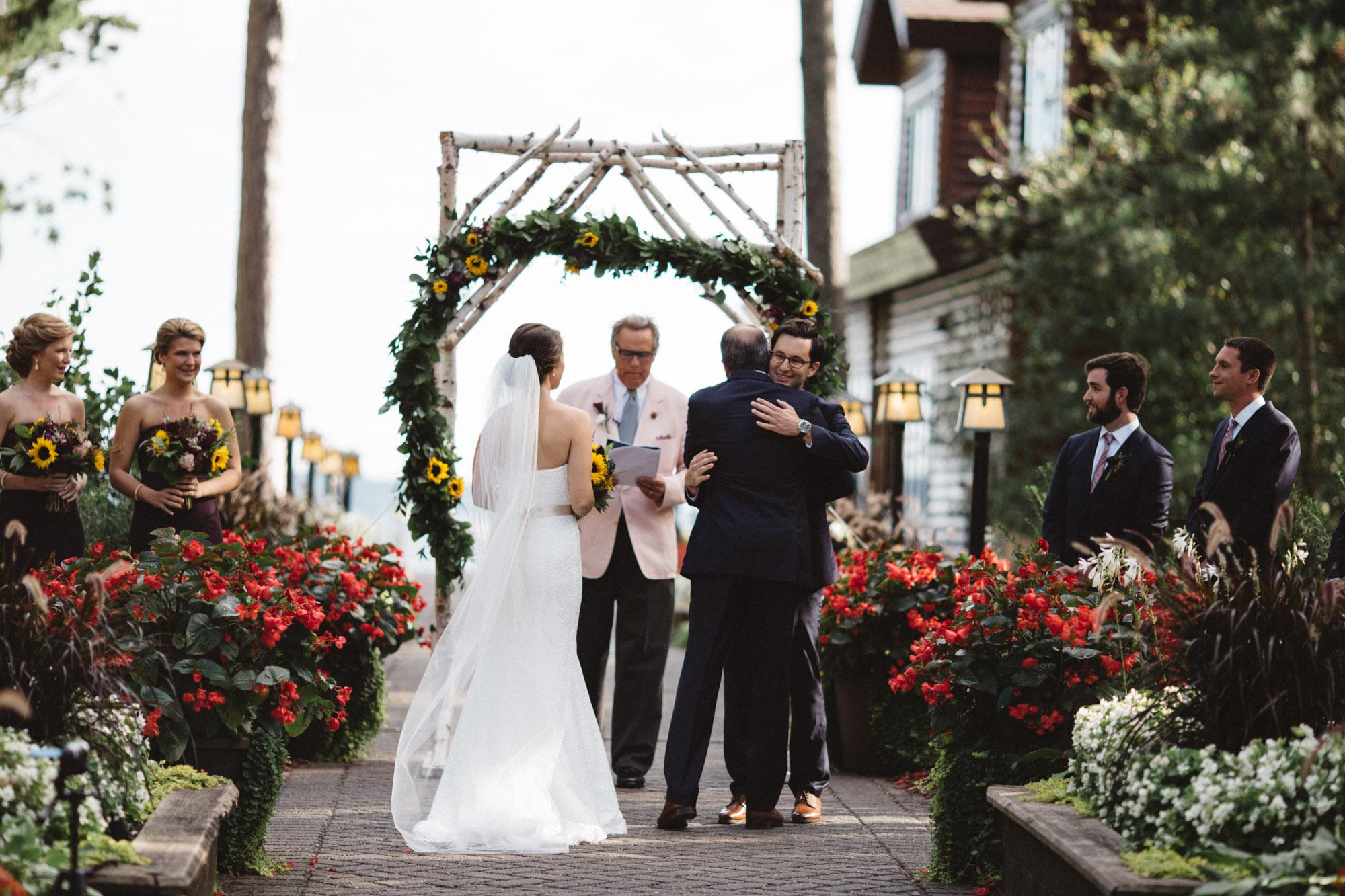 Father giving away bride to groom at wedding ceremony. Photography by Britt DeZeeuw, Brainerd Minnesota photographer