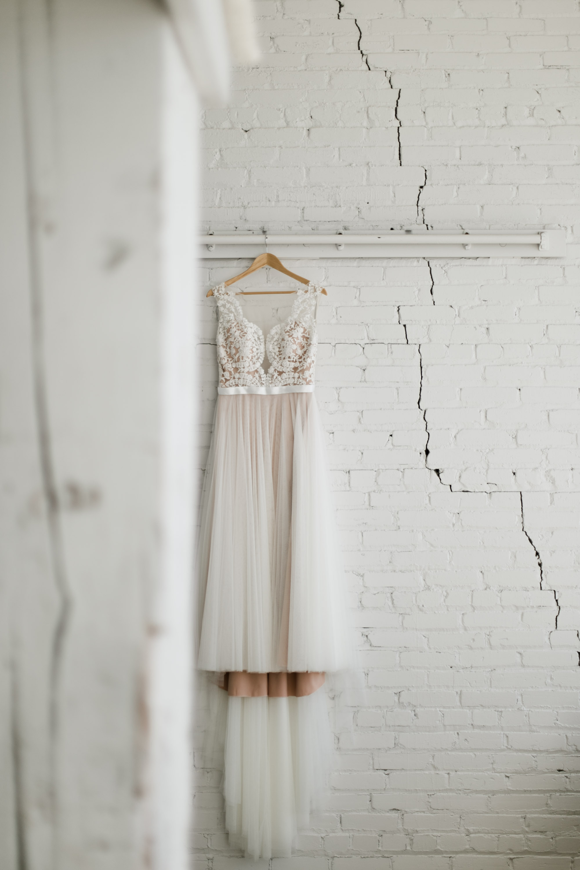 Boho chic wedding dressing hanging in the white bridal suite at the NP event space. Photography by Britt DeZeeuw.