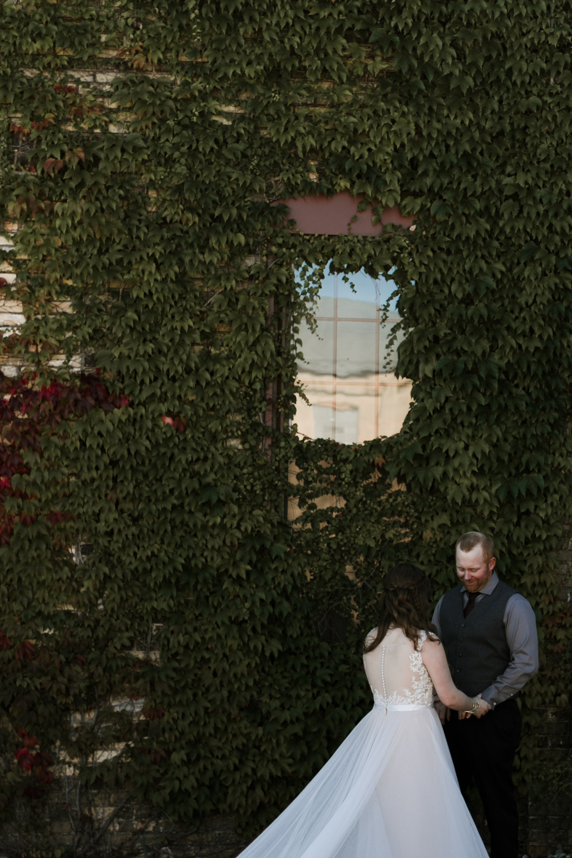 Bride and groom first look by the Ivy wall at the NP Event Space. Photography by Britt DeZeeuw, Brainerd MN wedding photographer.