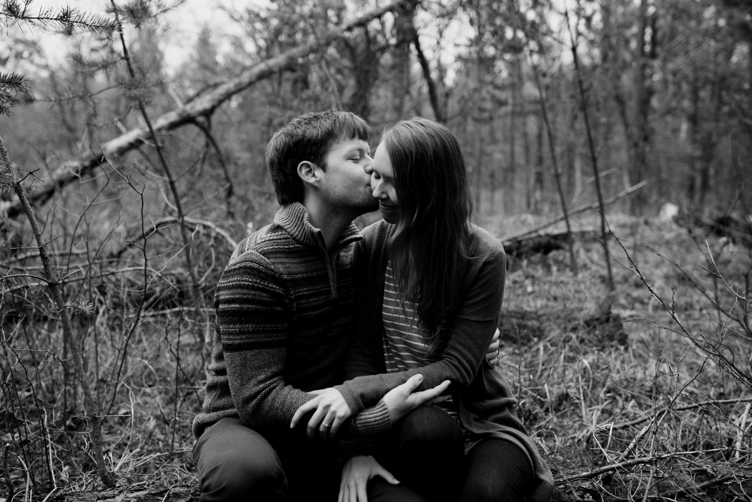 Black and white outdoor engagement photo outdoors in the woods at the Northland Arboretum in Brainerd Minnesota, photographed by wedding photographer Britt DeZeeuw Photography.