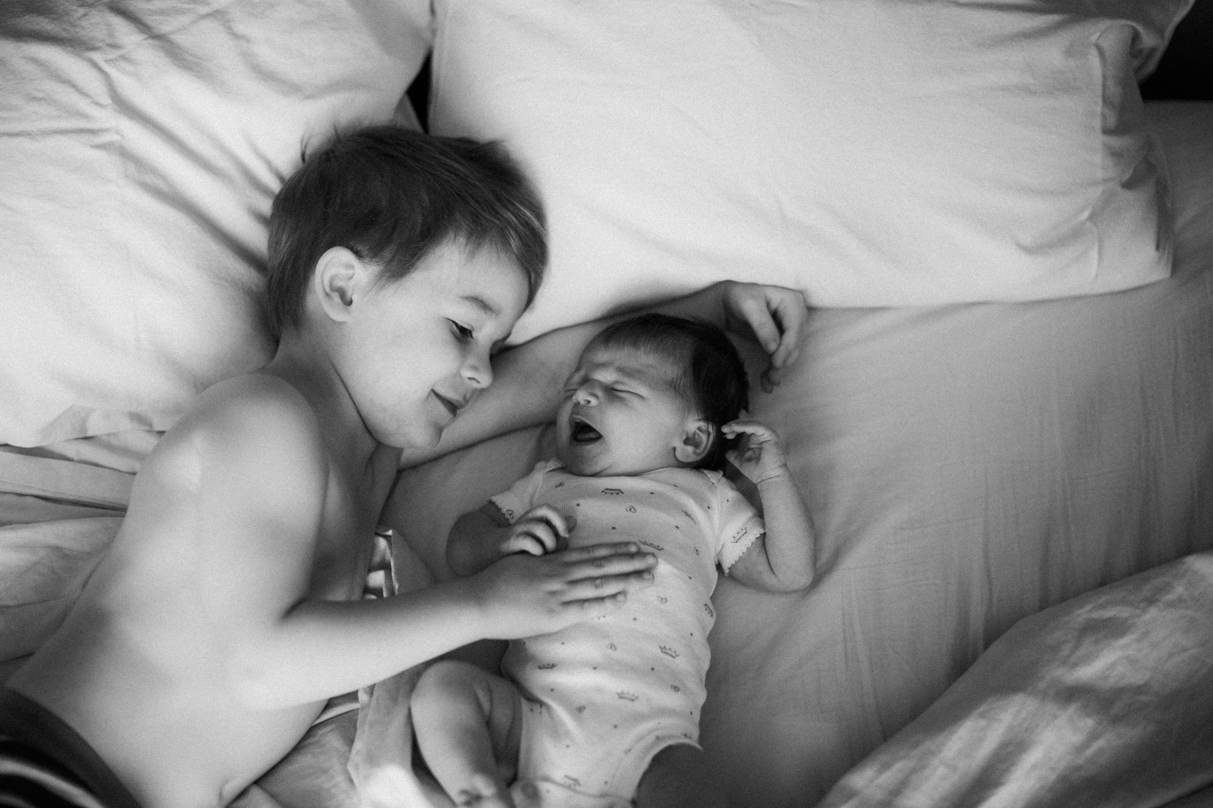 In home documentary family photography of brother and newborn sister by Brainerd photographer Britt DeZeeuw