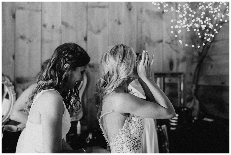 Emotional bride getting in dress at Creekside Farm barn wedding in Rush City, Minnesota